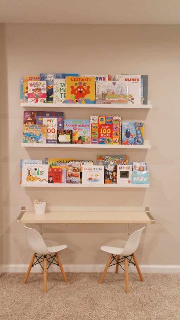 Books on a shel with a desk and two chairs | Basement Playroom