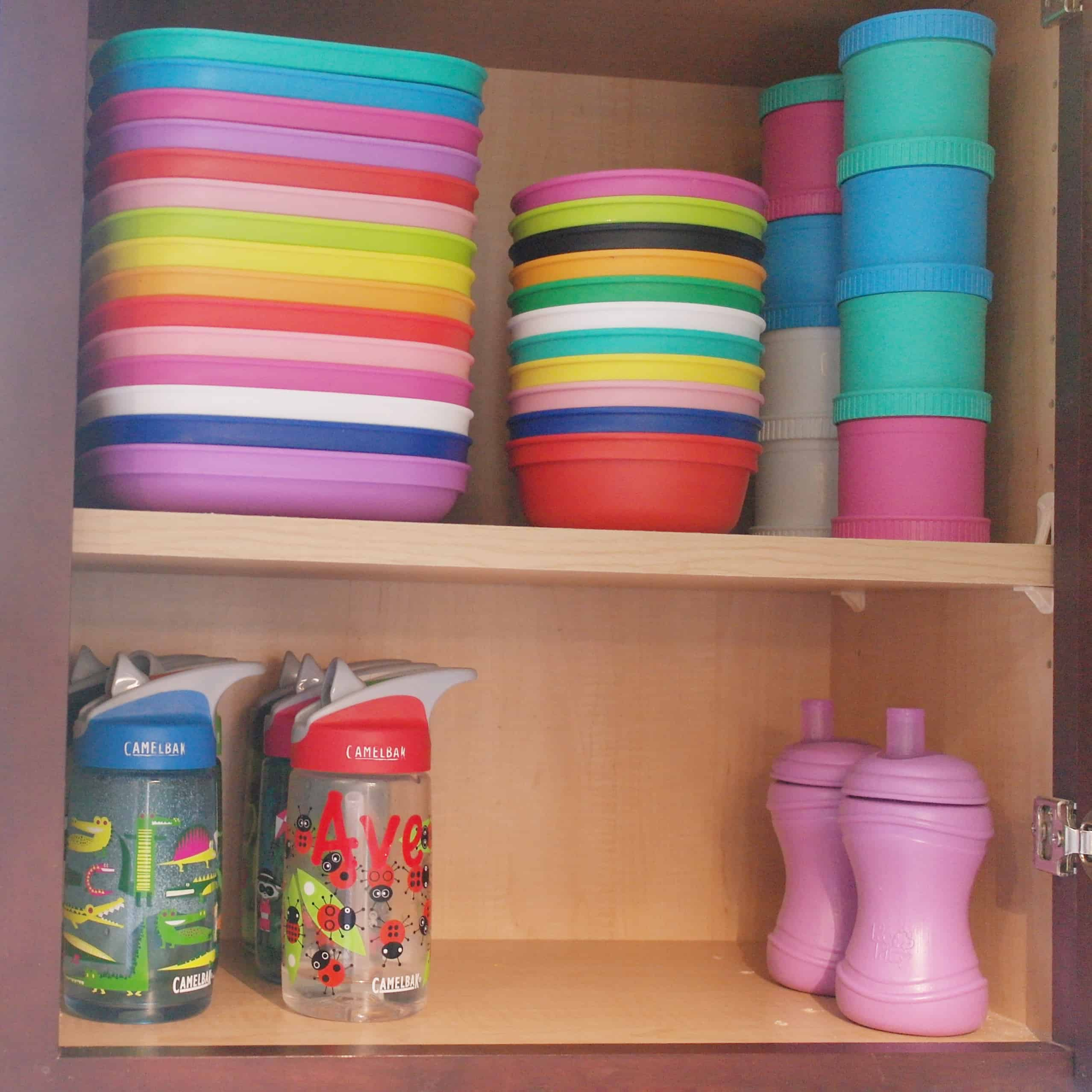 inside of kitchen cupboard with kids items