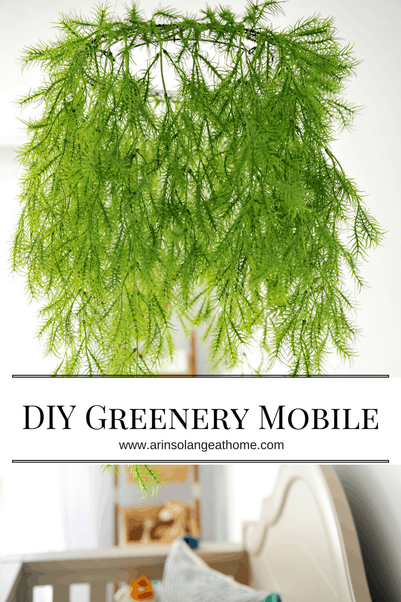 faux greenery mobile over crib with text overlay