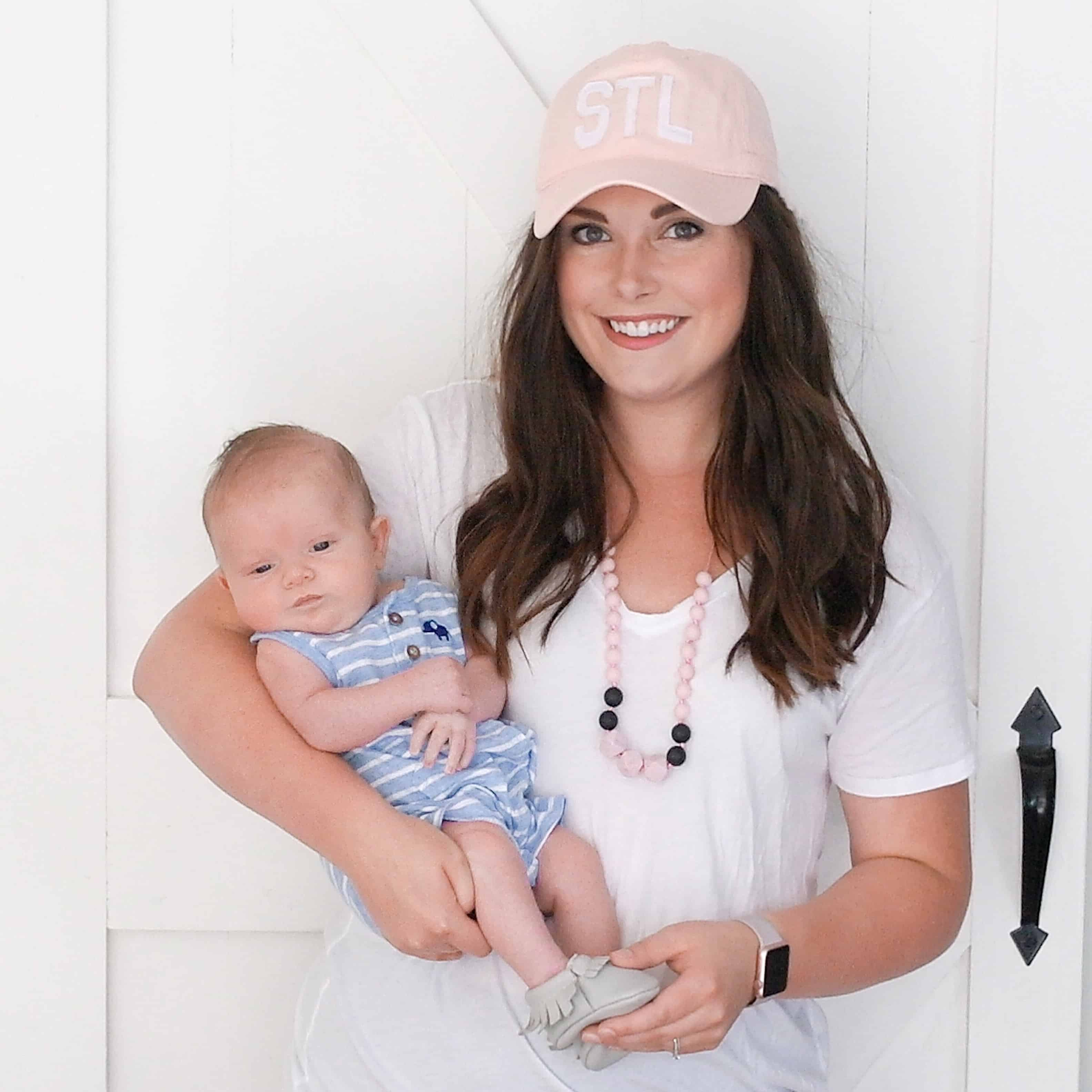 mom holding baby in STL hat | New Mom Must Haves