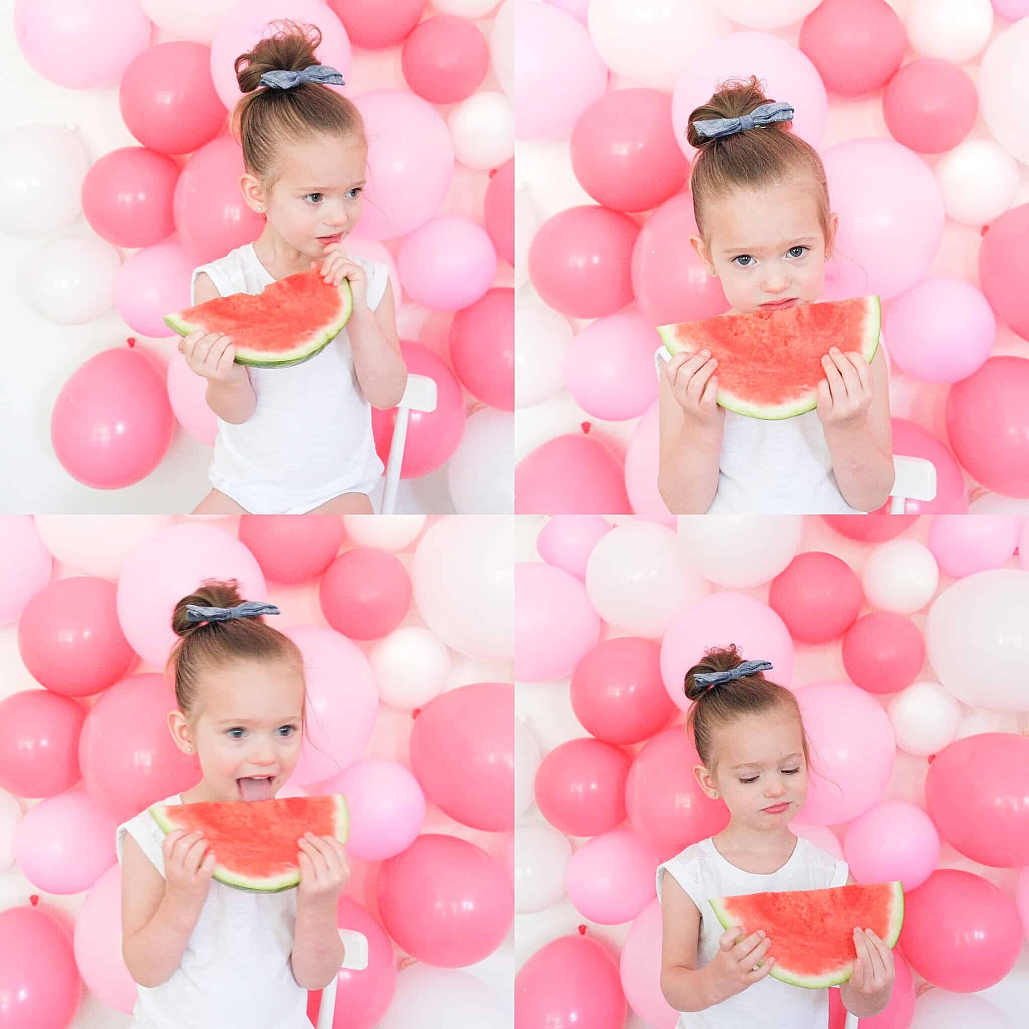 little girl eating watermelon in front of pink DIY balloon wall