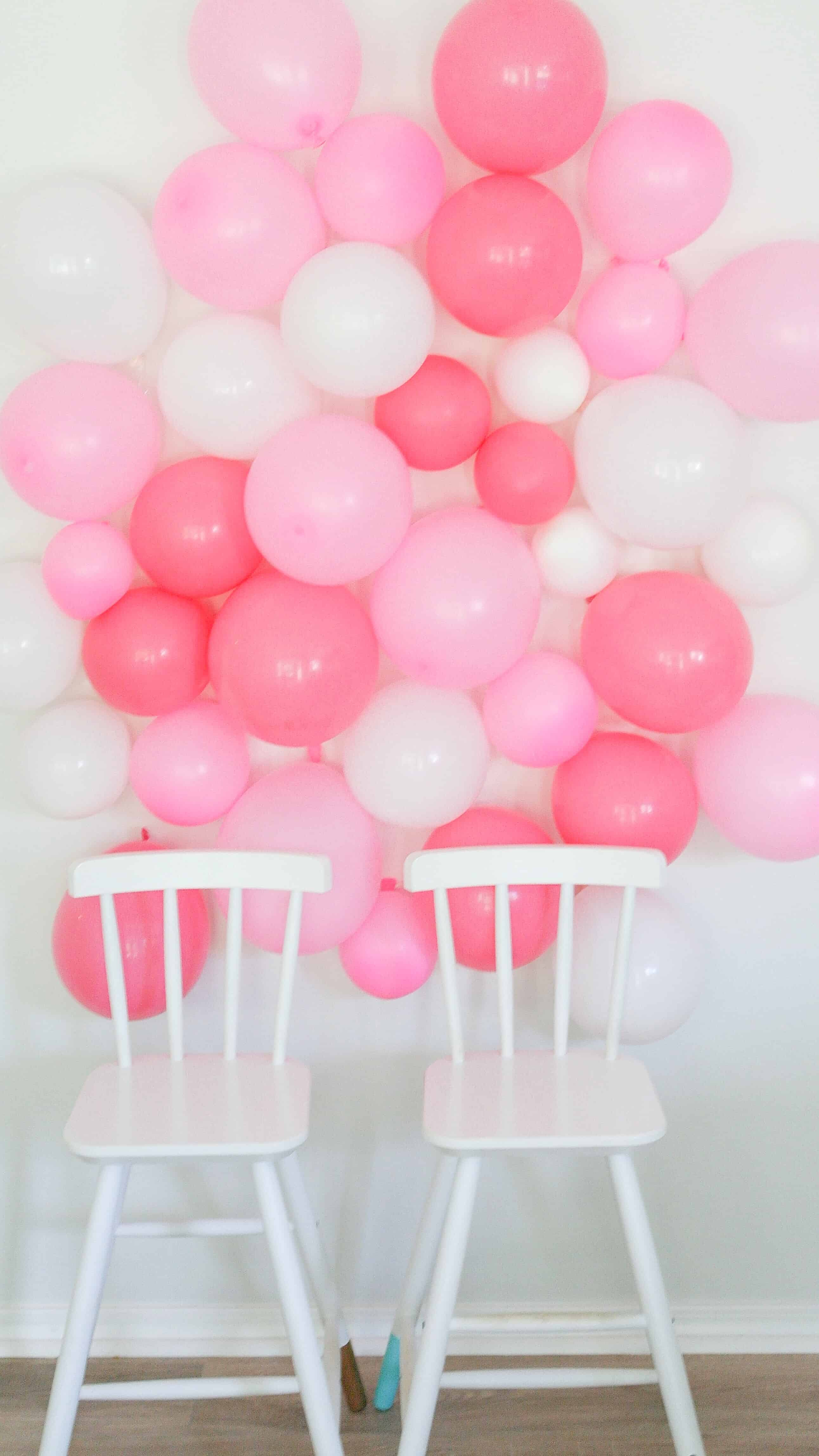 white chairs in front of pink and white DIY balloon wall
