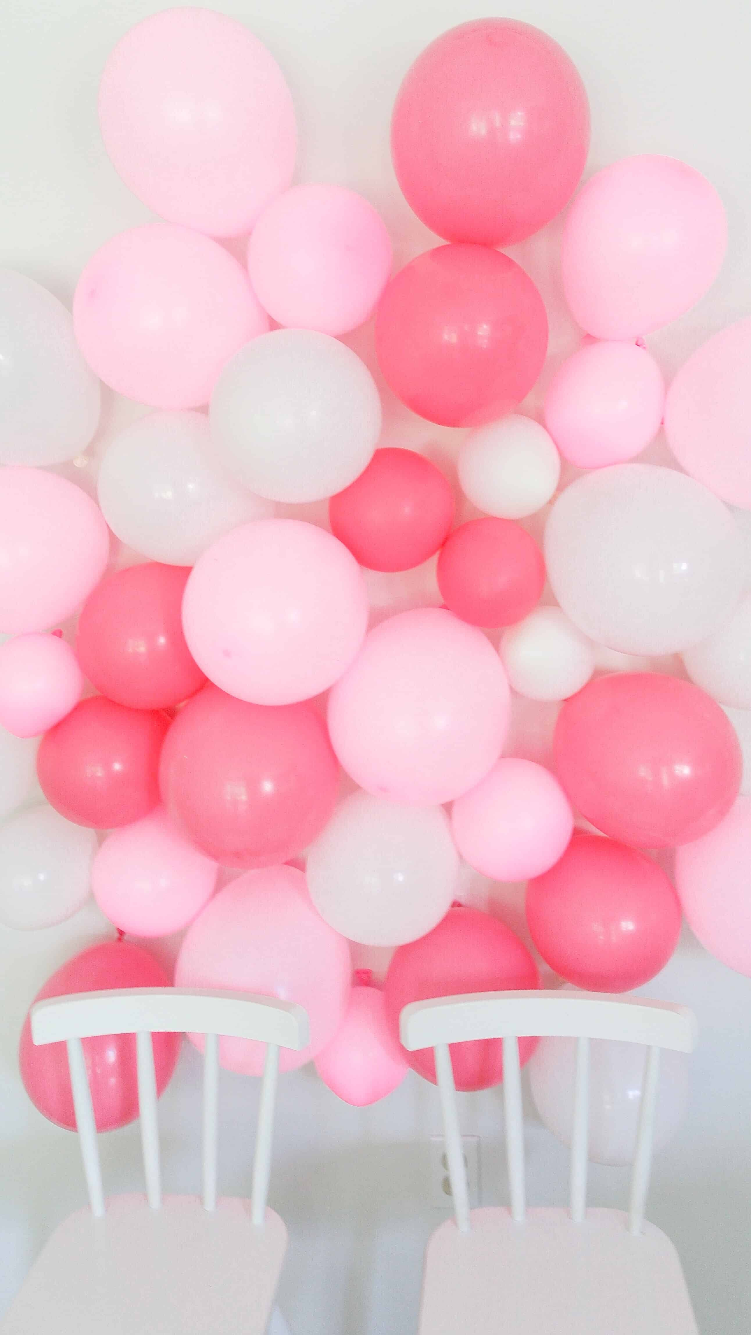white chairs in front of white and pink DIY balloon wall