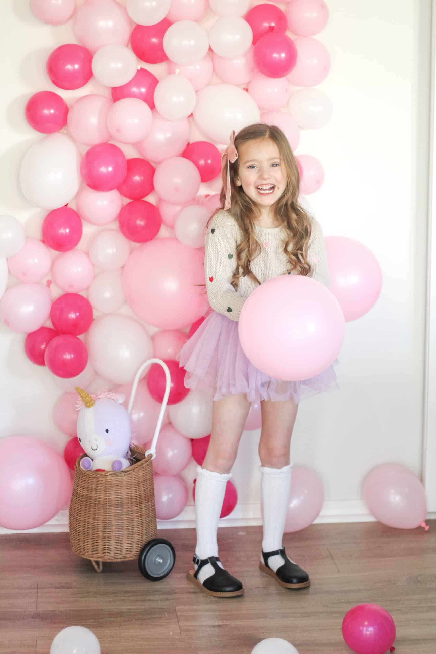 toddler girl in front of pink balloon photo wall