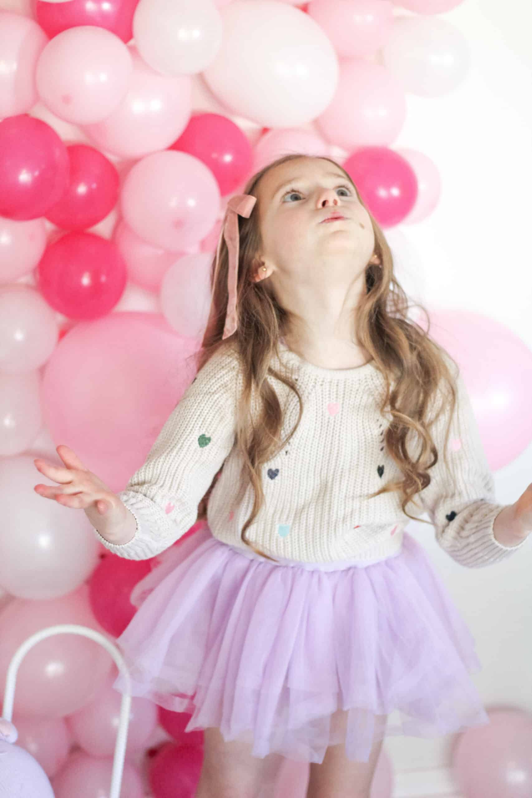 toddler girl in sweater in front of pink balloon wall