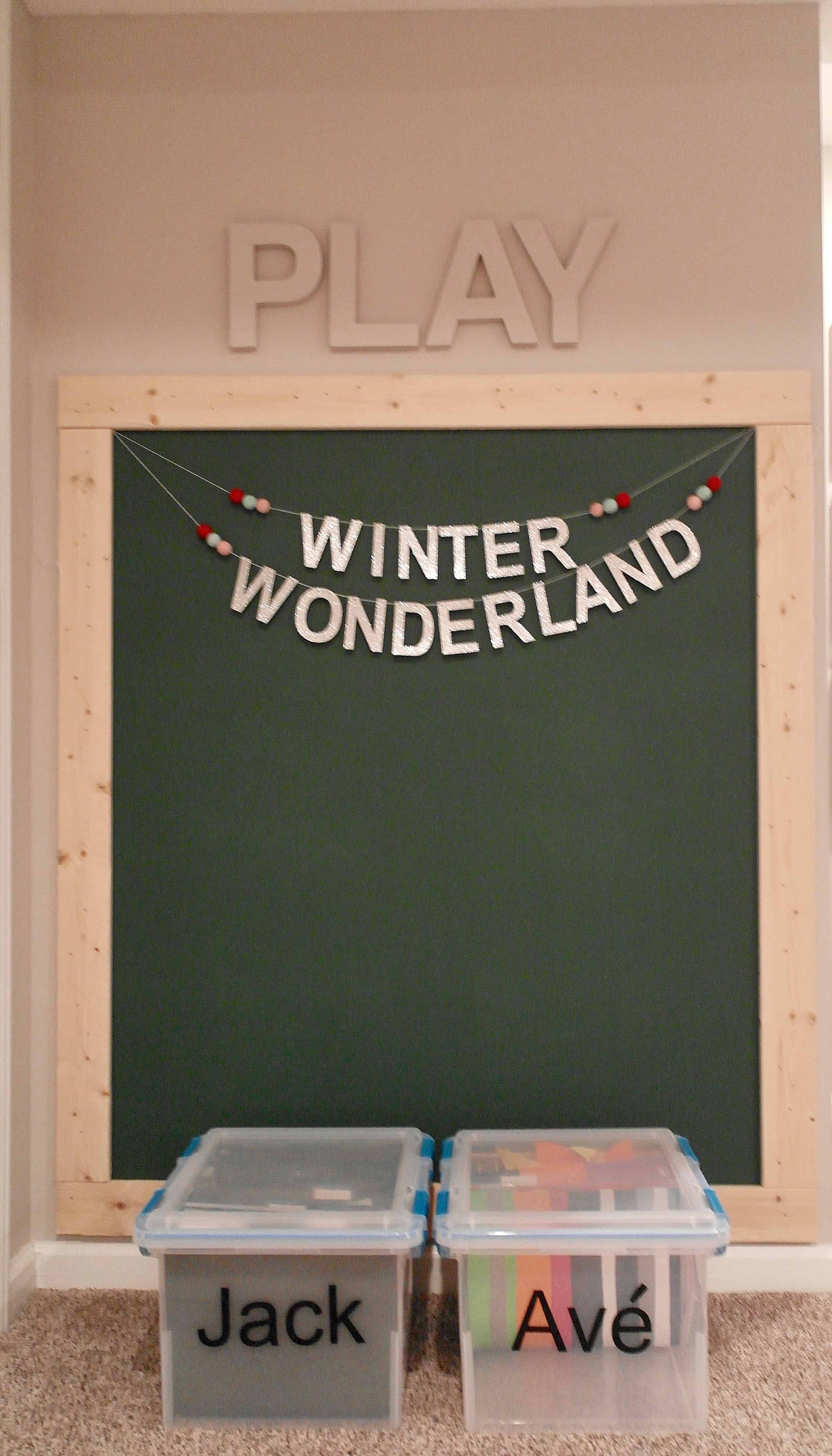large chalkboard wall with bins for kids artwork