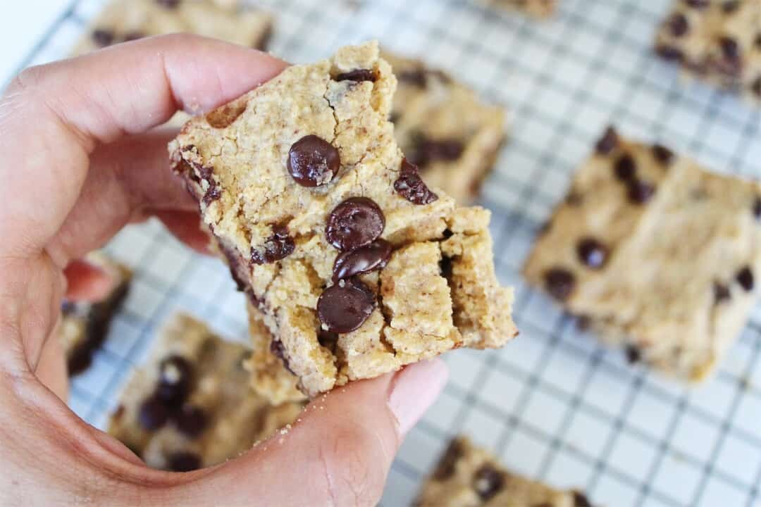 person holding gluten free chocolate chip cookie bar over baking pan