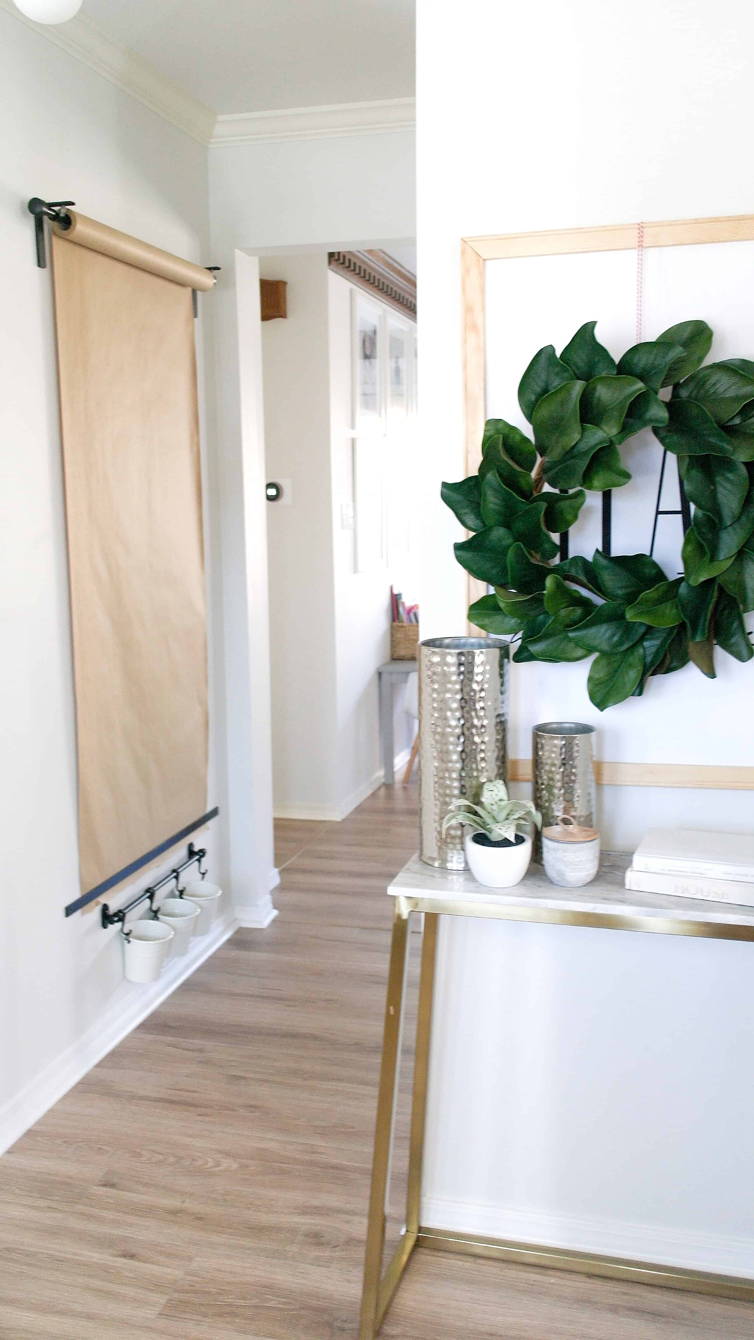 Entry way table with wreath and wall mounted paper roll and bins. Lifestyle blogger Arin Solange shares an Ikea Hack, how to create the perfect DIY Wall mounted Easel.