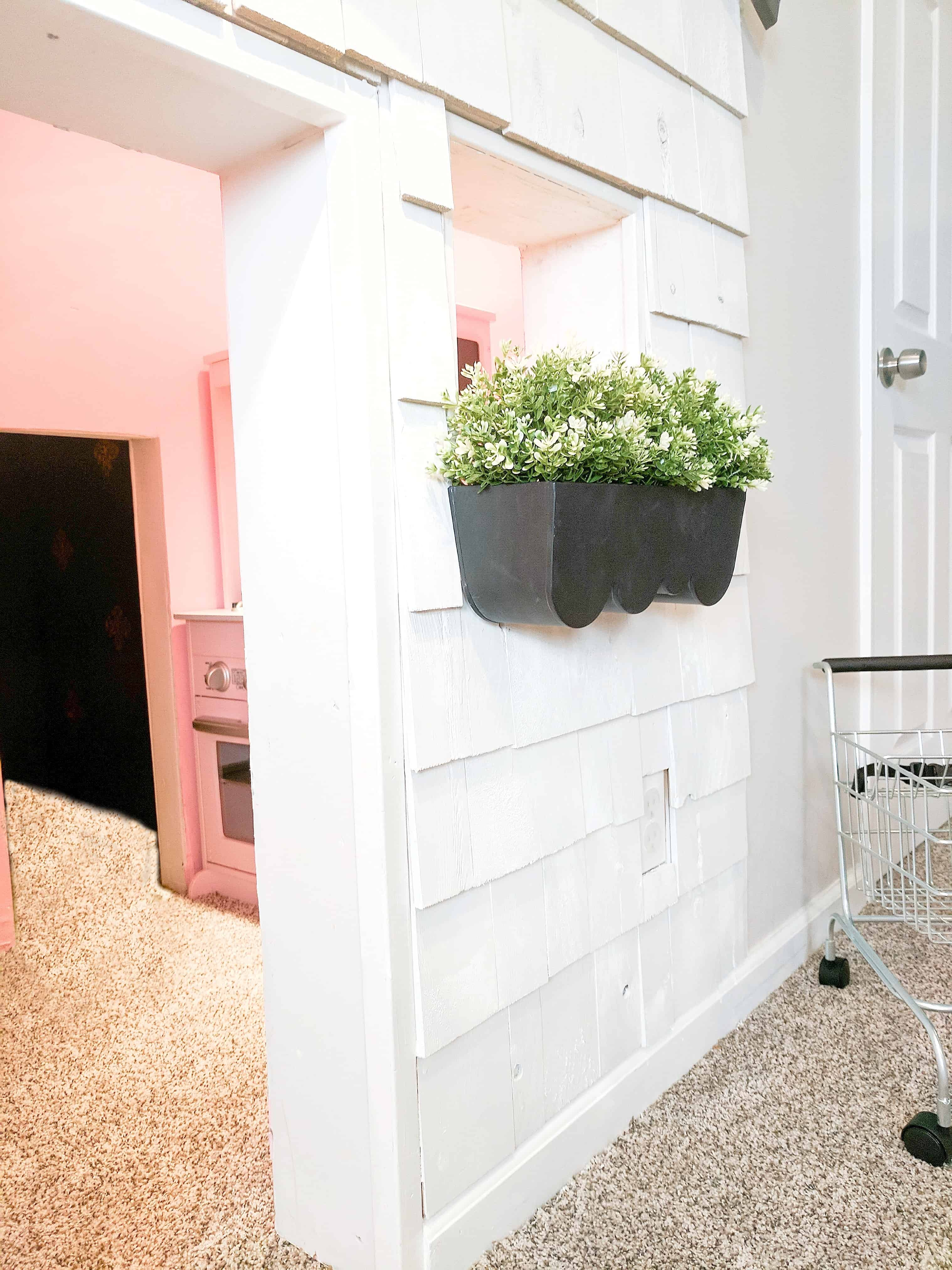 white shingle under stairs playhouse with pink walls