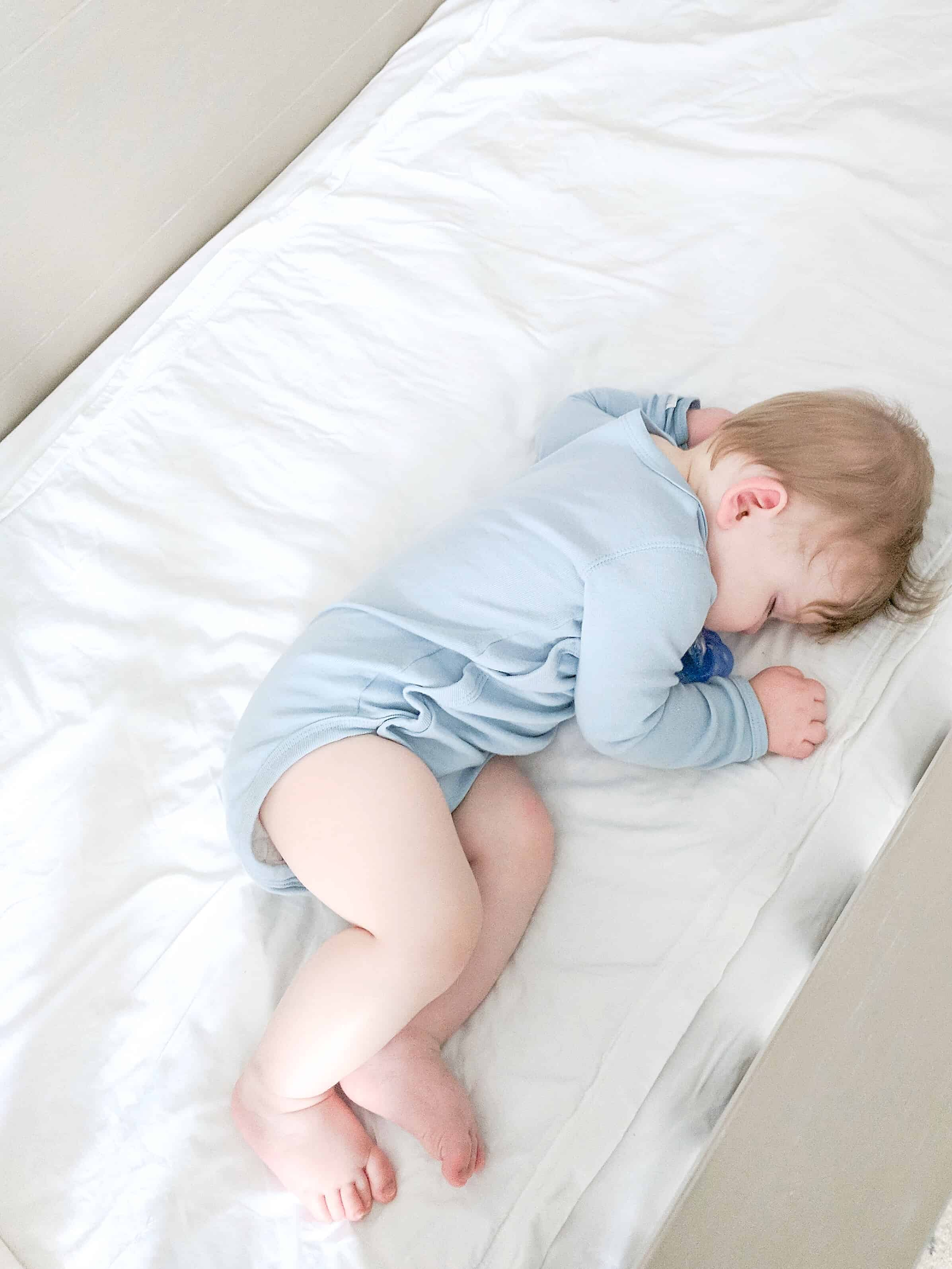 sleeping baby in blue onsie on white sheets