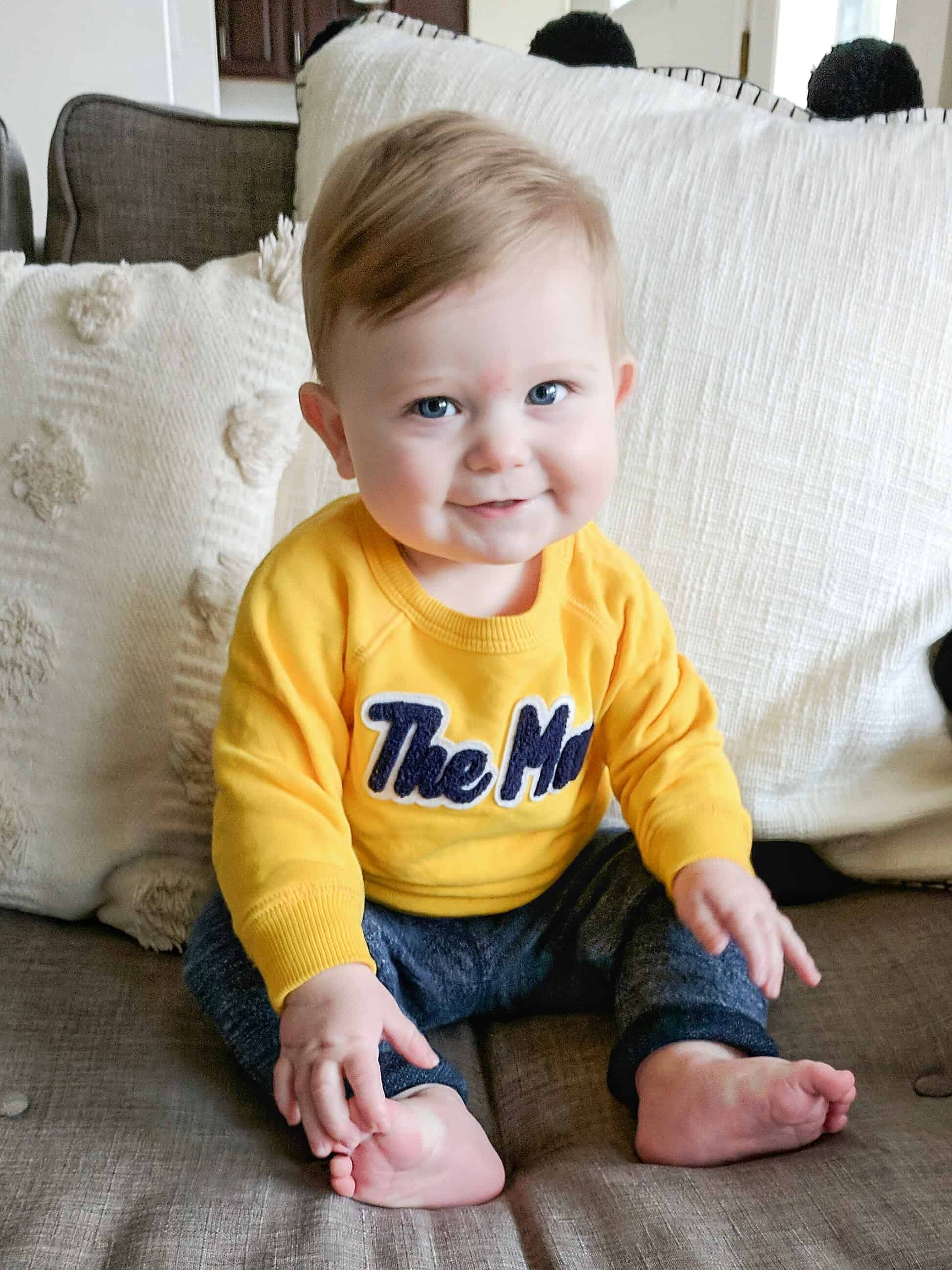 baby boy in yellow sweatshirt on couch