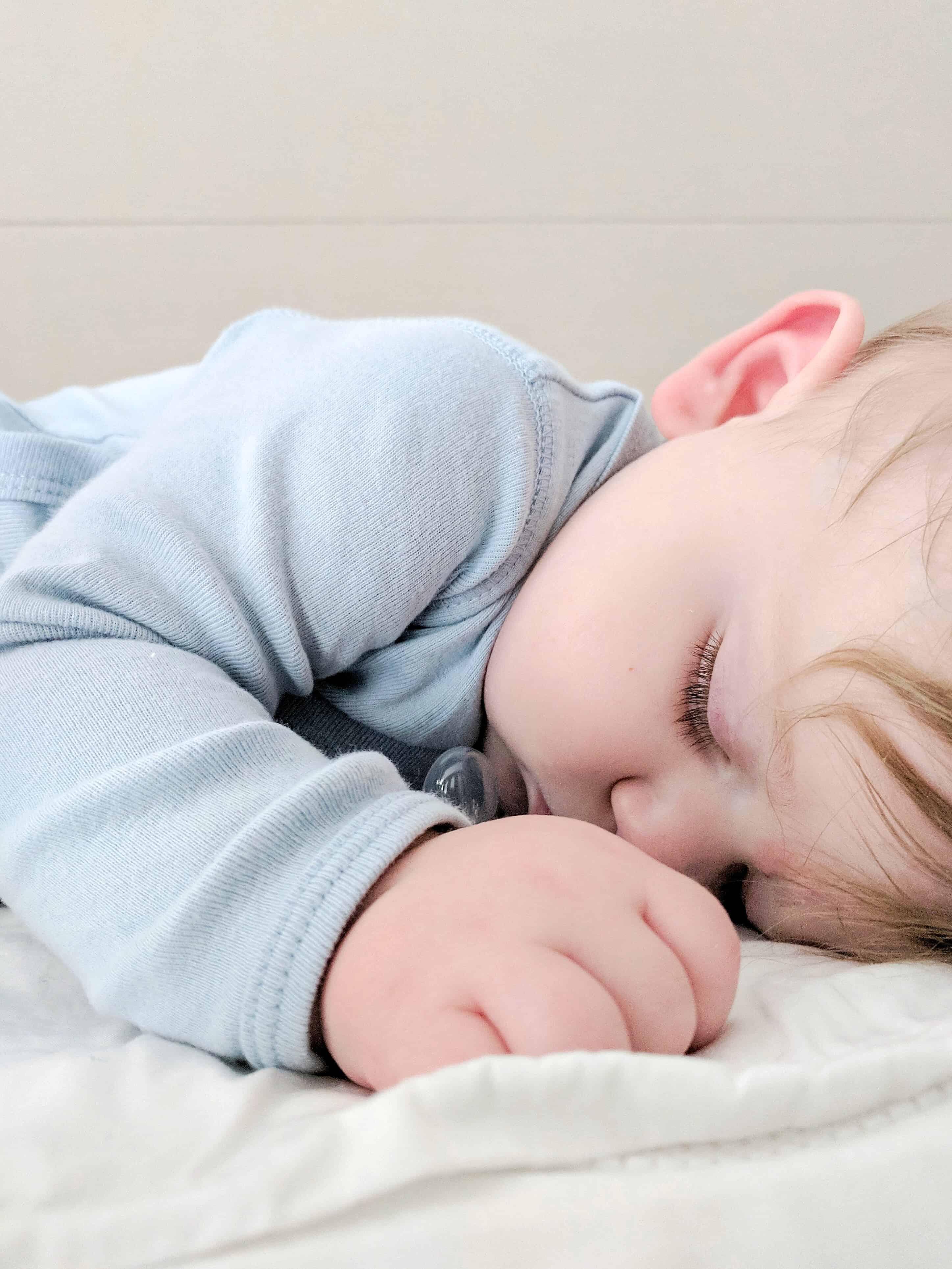 sleeping baby in blue onsie