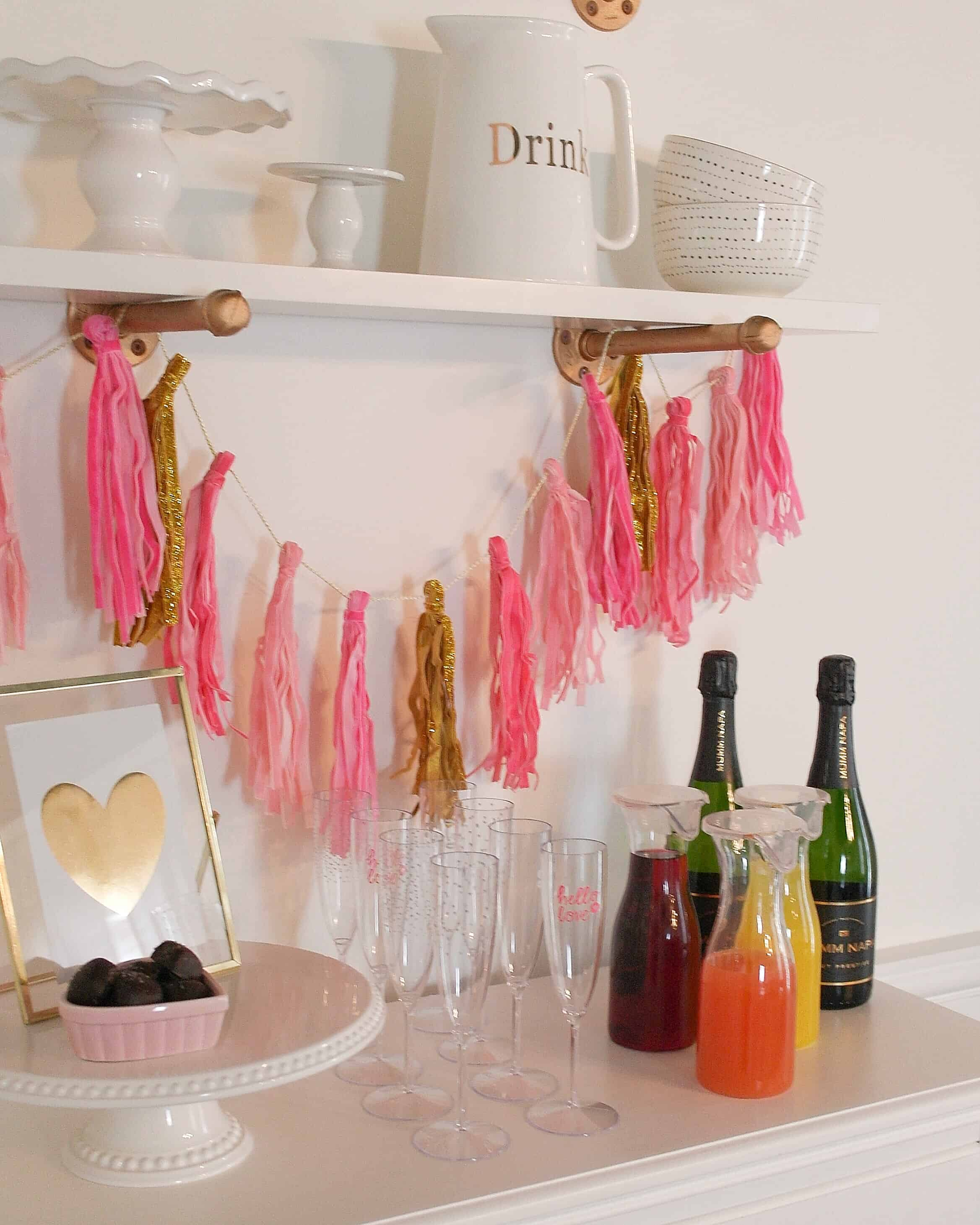pink banner, juice, champagne on white chest of drawers | Valentine's Day Party