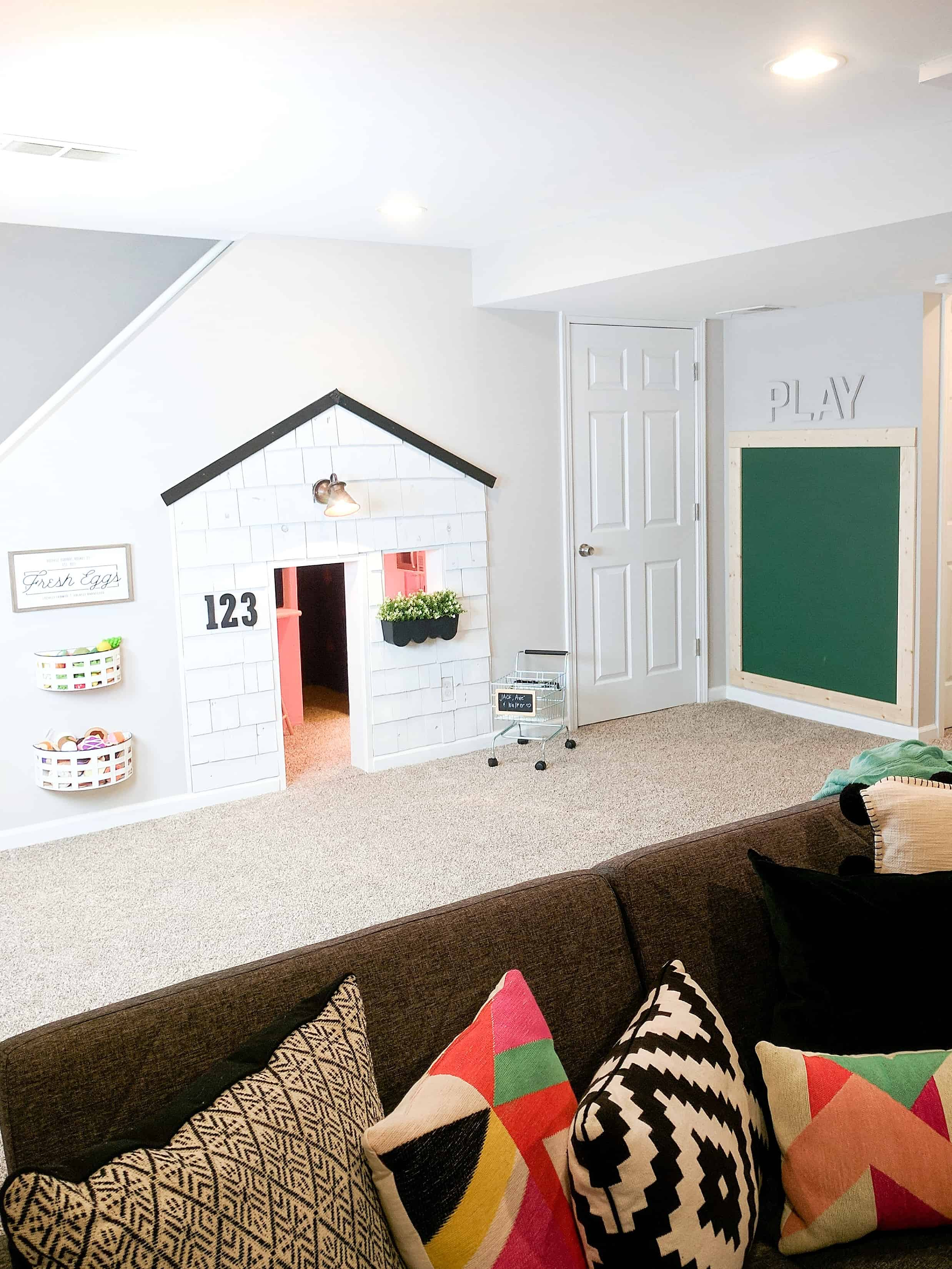 playroom with built in under stairs playhouse house and chalkboard wall