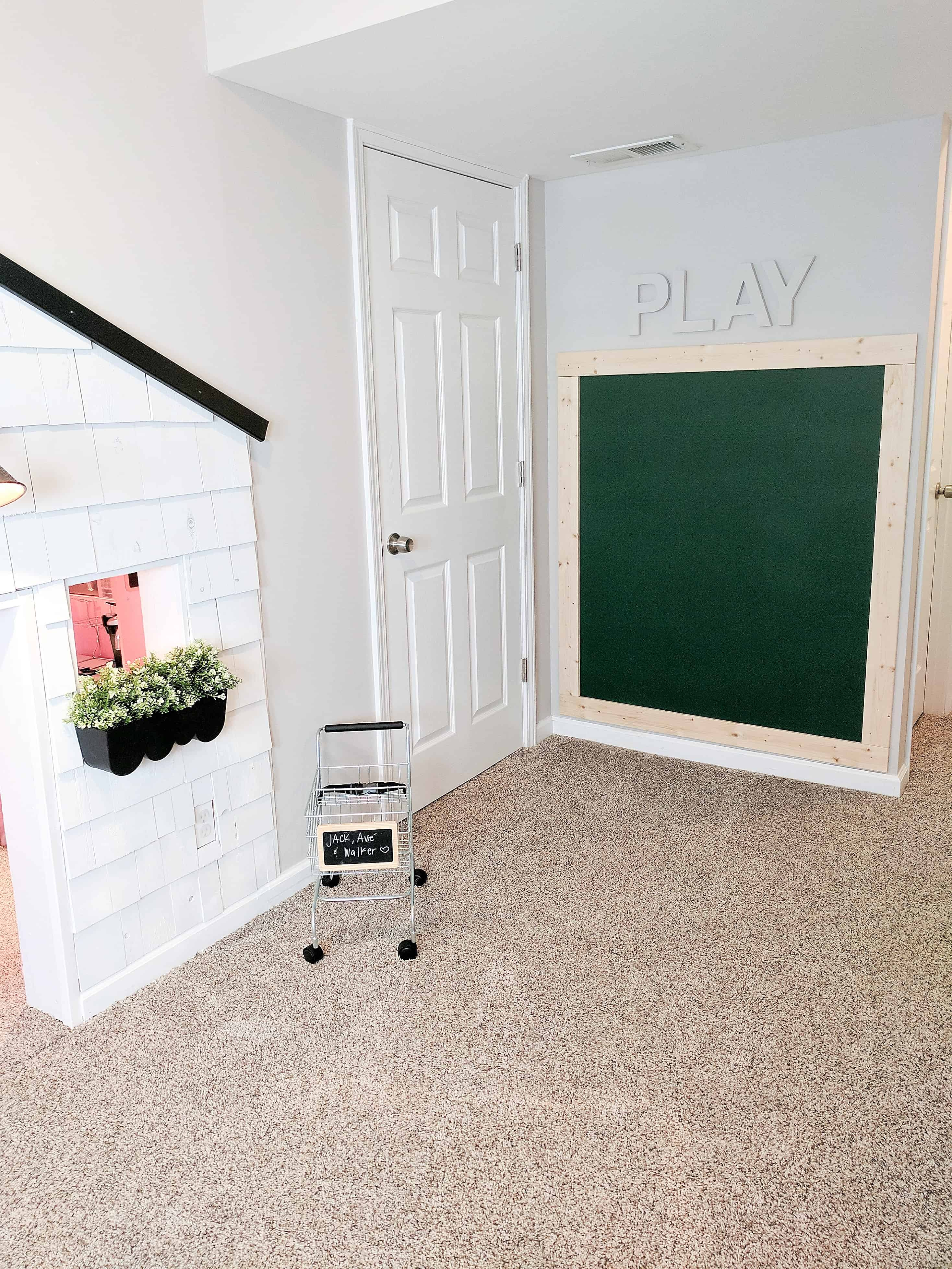 white playhouse with grocery cart and framed green chalk wall in our basement with our under stairs built in playhouse