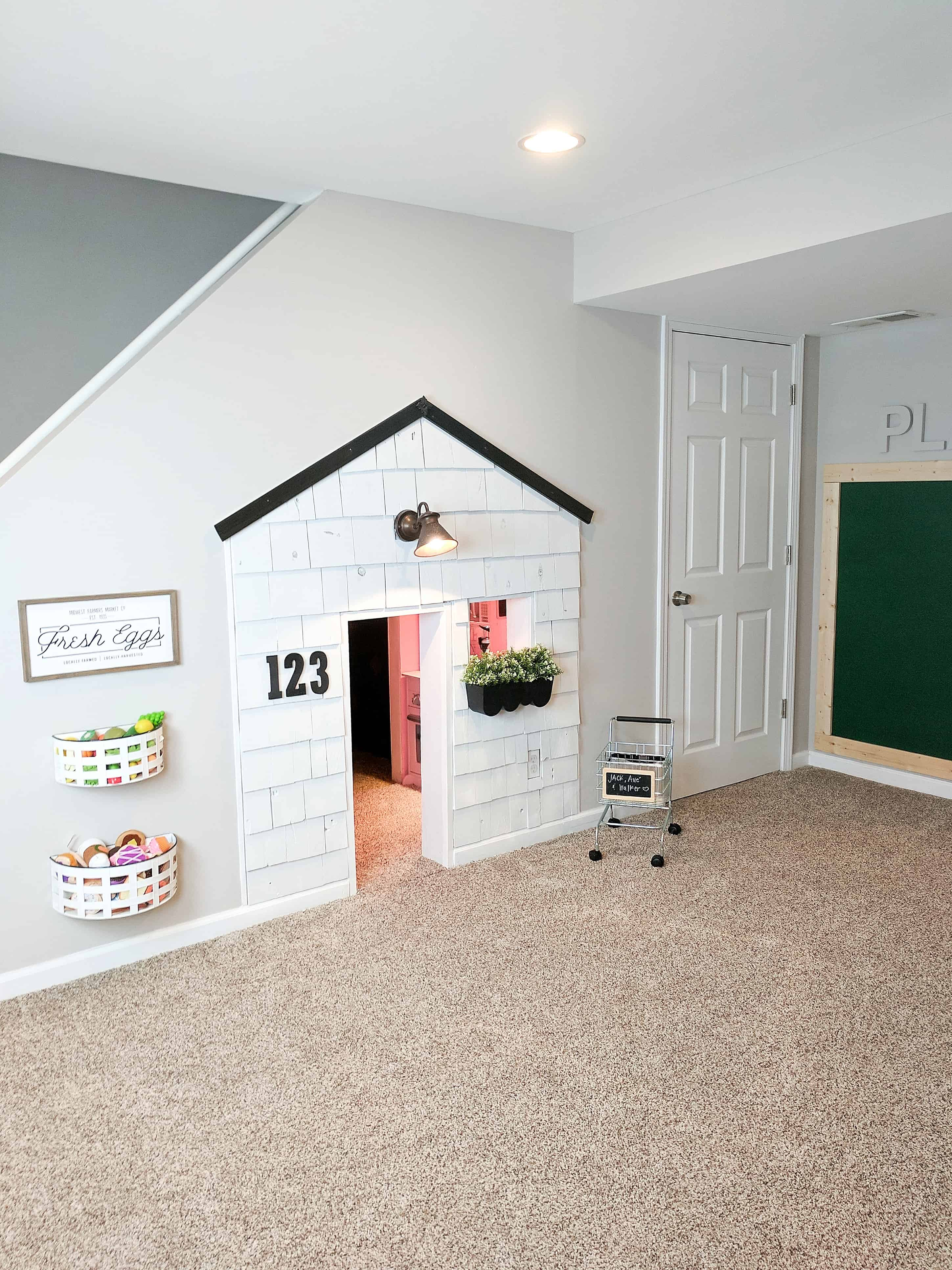 room with white shingle playhouse shopping cart and bins on wall in our basement with our under stairs built in playhouse