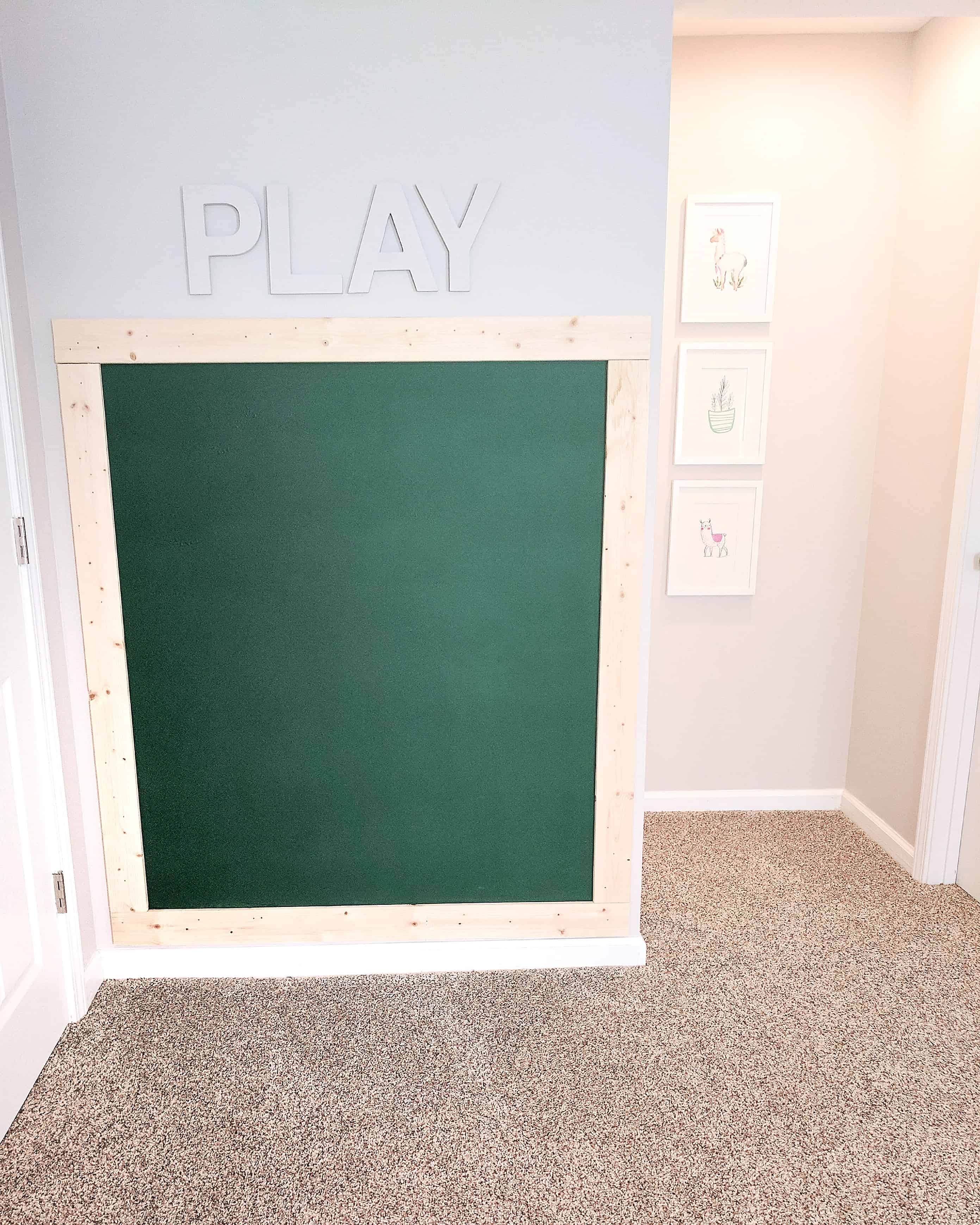 framed green chalk wall with the word PLAY over it in our basement with our under stairs built in playhouse