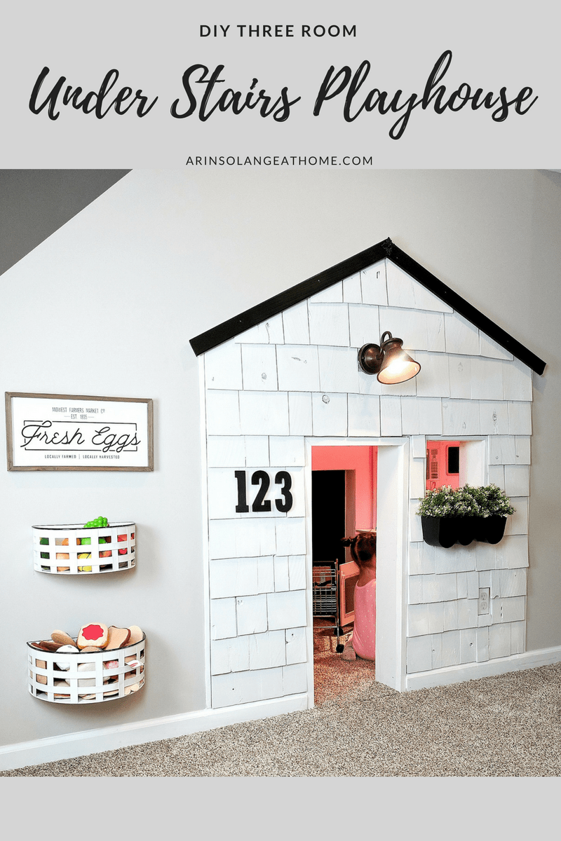 room with white shingle playhouse shopping cart and bins on wall