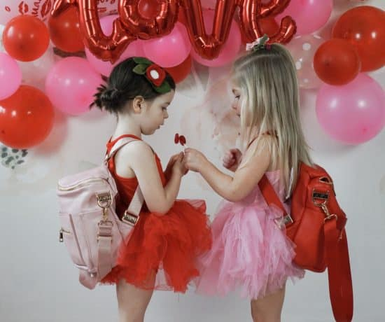 two toddlers in front of pink and red balloons with fawn design mini bags
