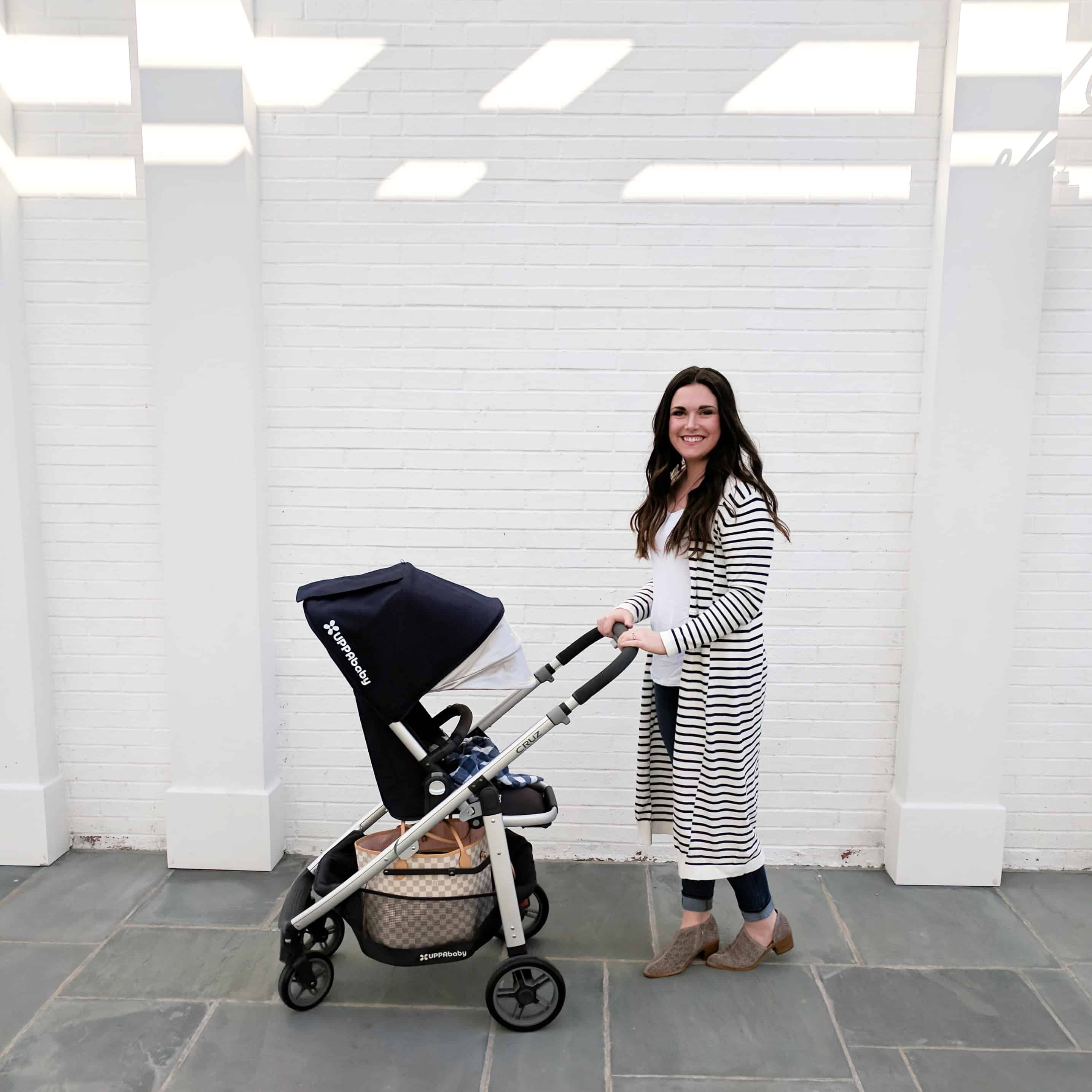 mom pushing stroller by white wall | Buying a Stroller