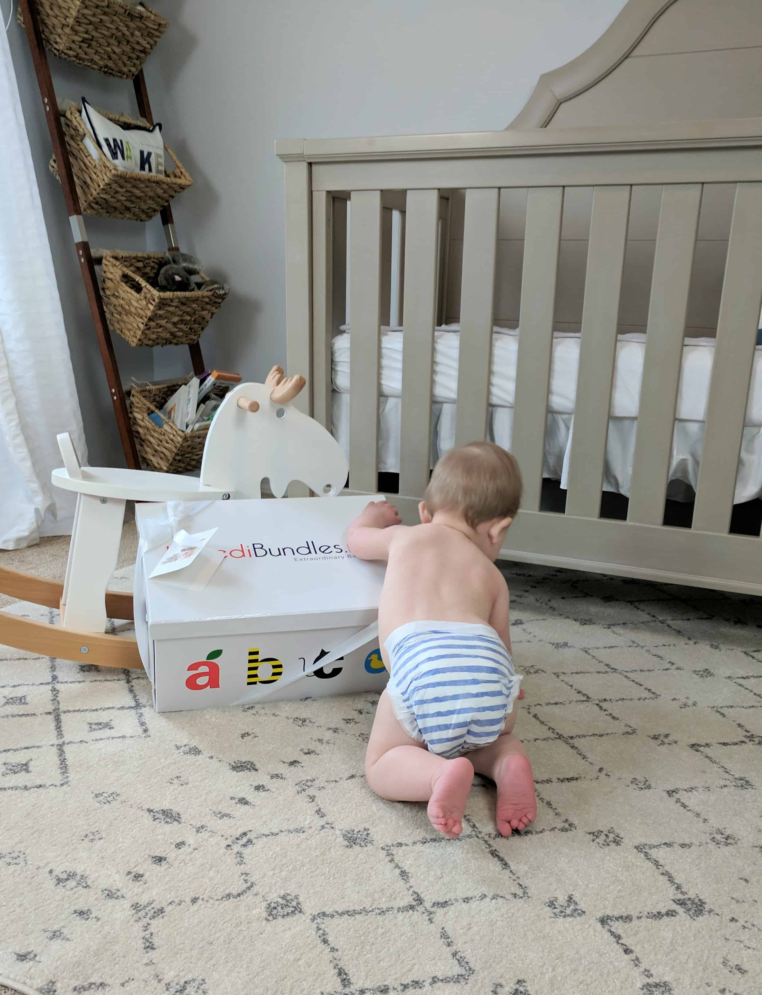 Baby opening box by rocking horse and crib