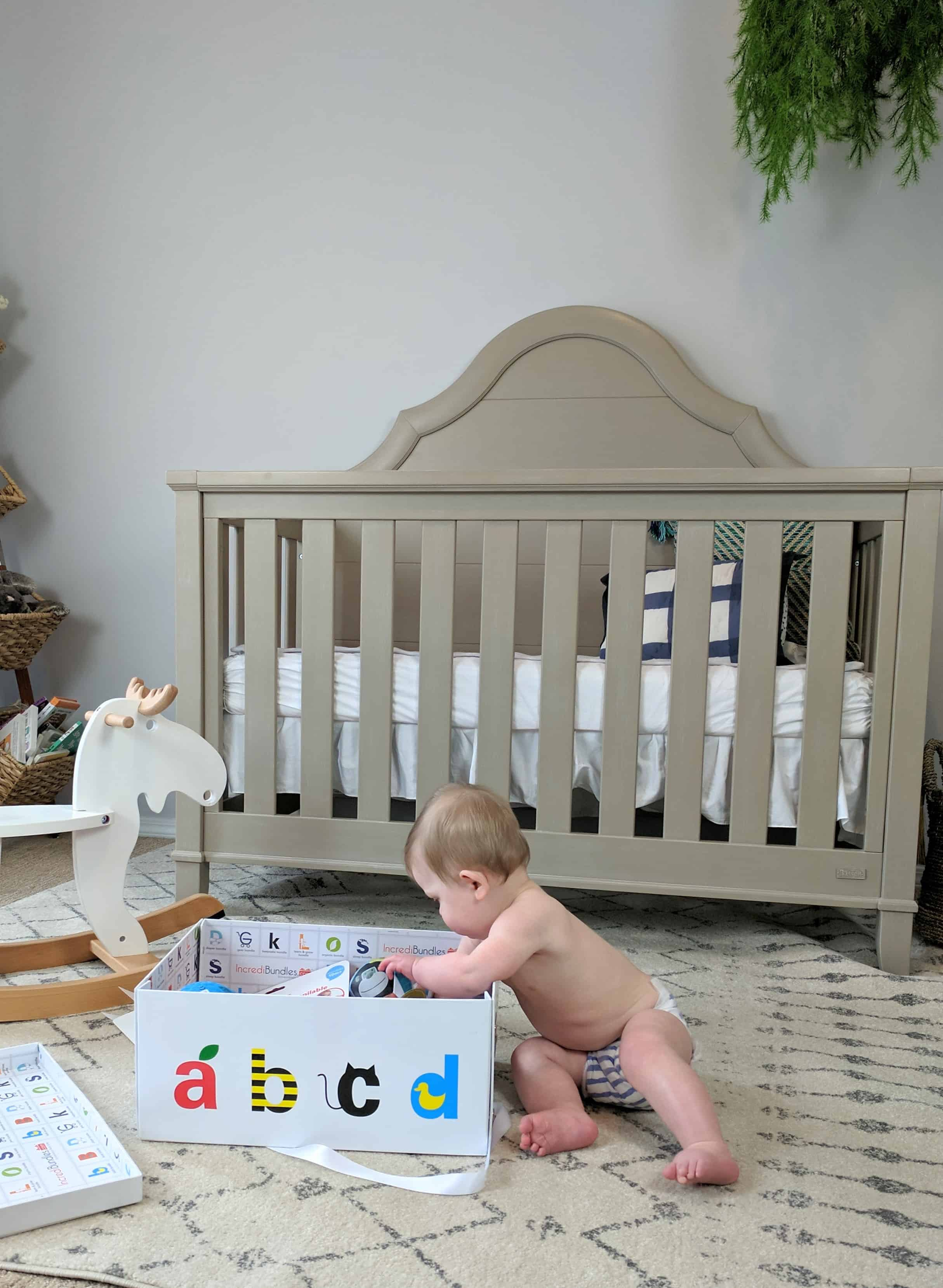 baby digging into box of gifts by rocking horse and crib