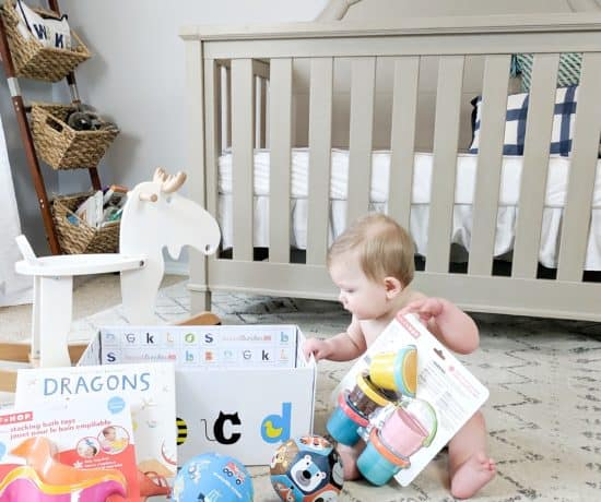 Baby on floor by rocking horse and crib with gifts