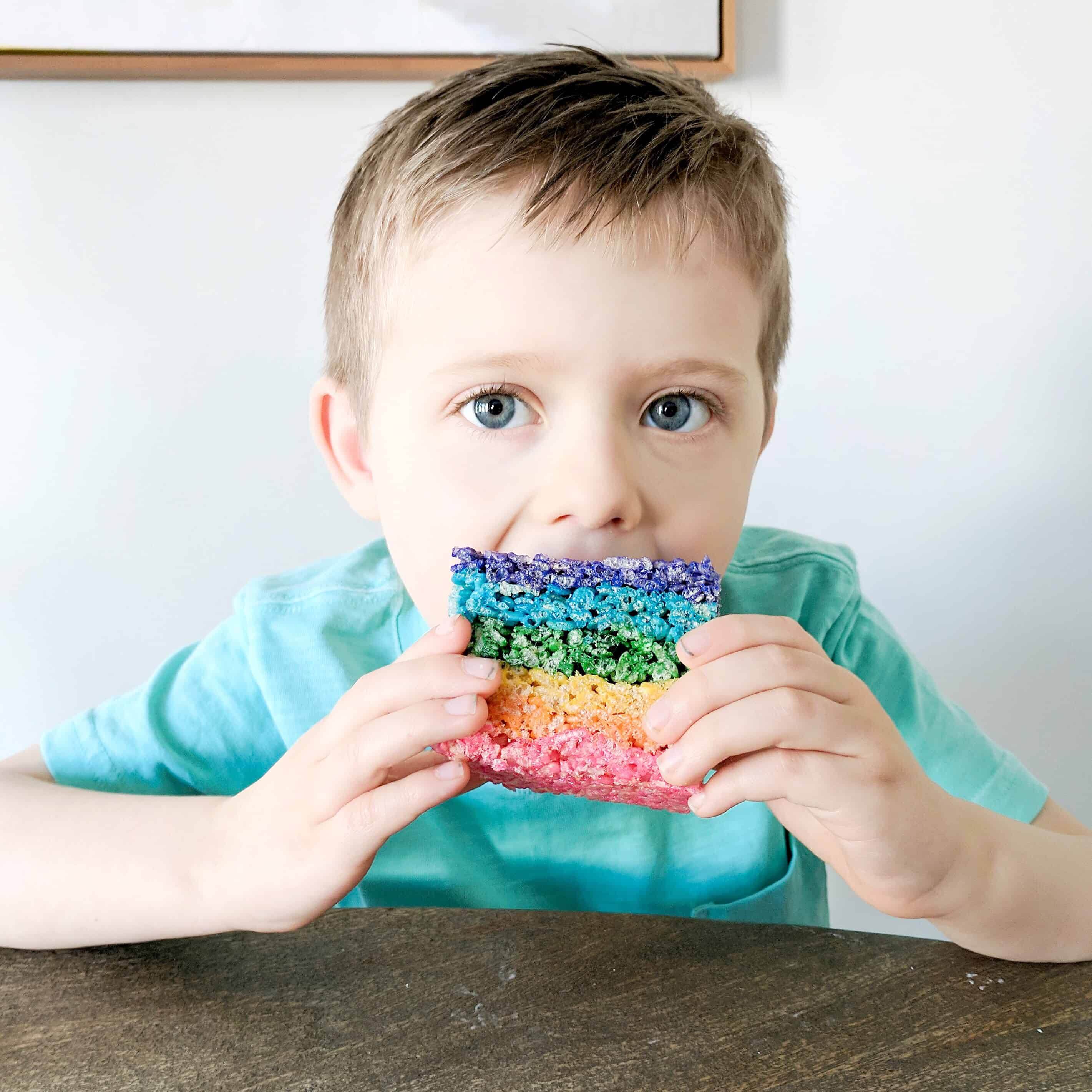 boy in green shirt eating rainbow rice Krispy treat