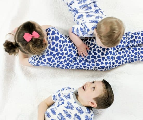 three kids laying on bed in matching pajamas