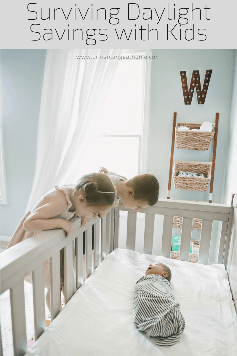 two toddlers looking at baby in a crib
