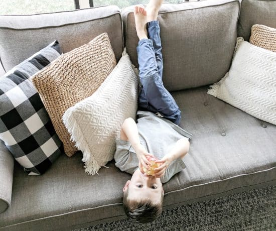 little boy eating apple on grey couch
