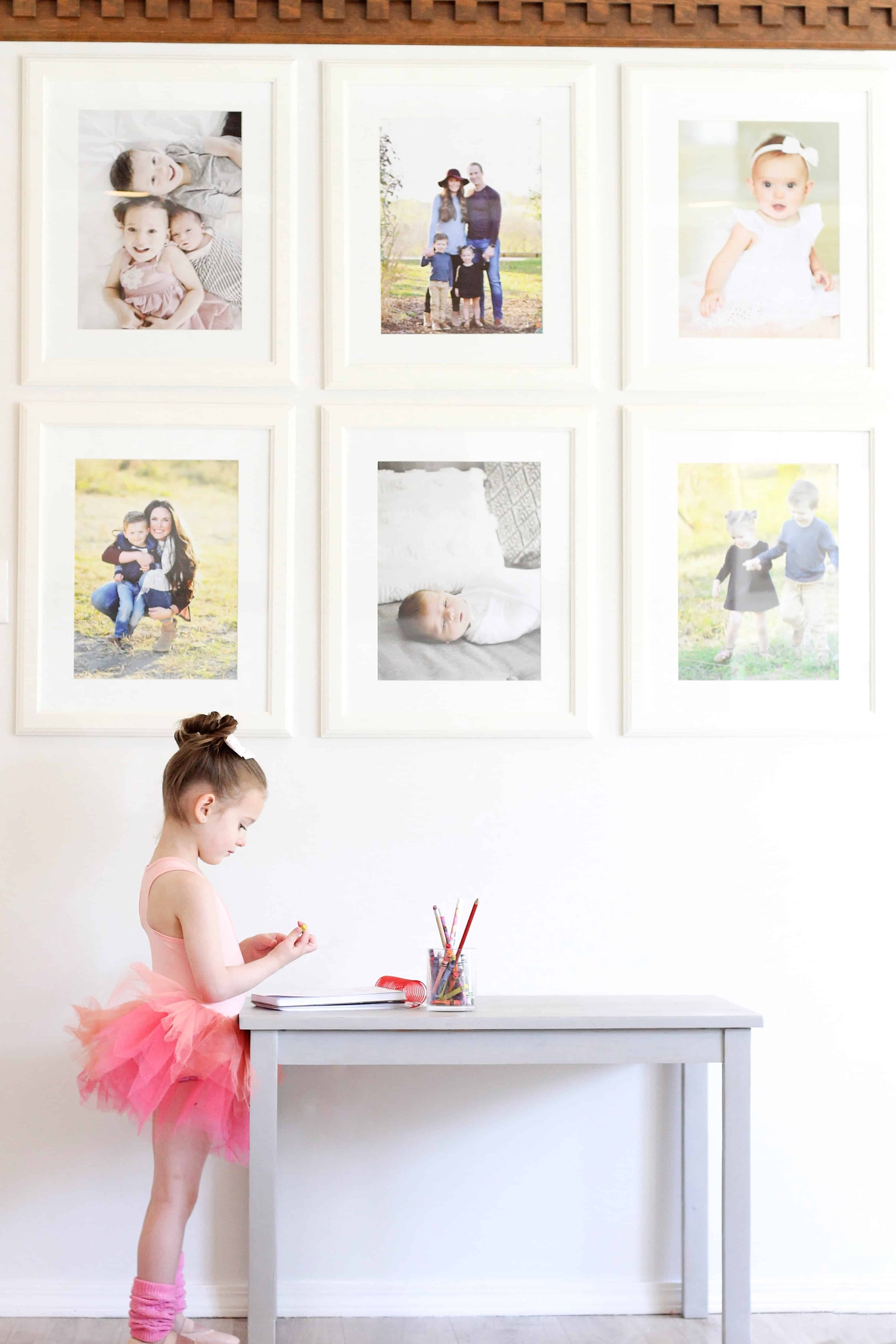 little girl in plum tutu standing by photo wall