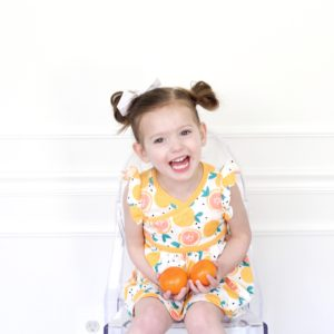 toddler girl in clementine dress from tea collection