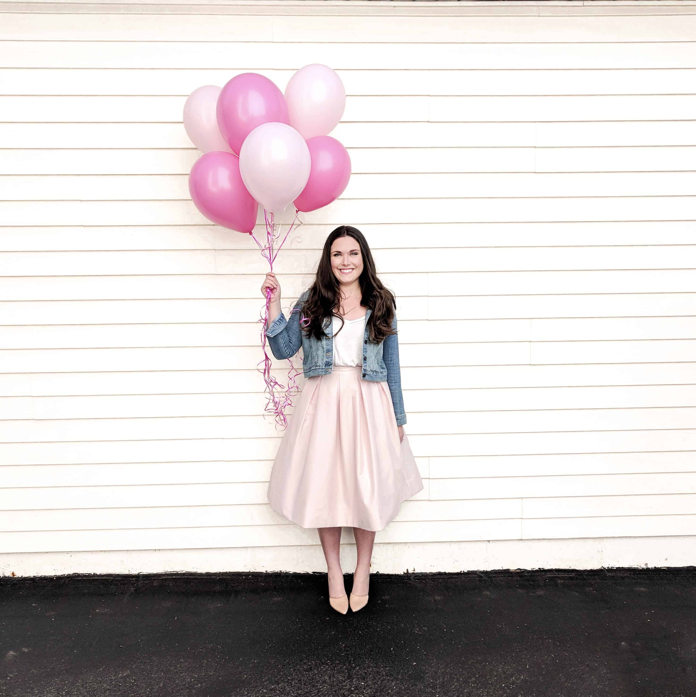 woman in pink skirt holding pink balloons