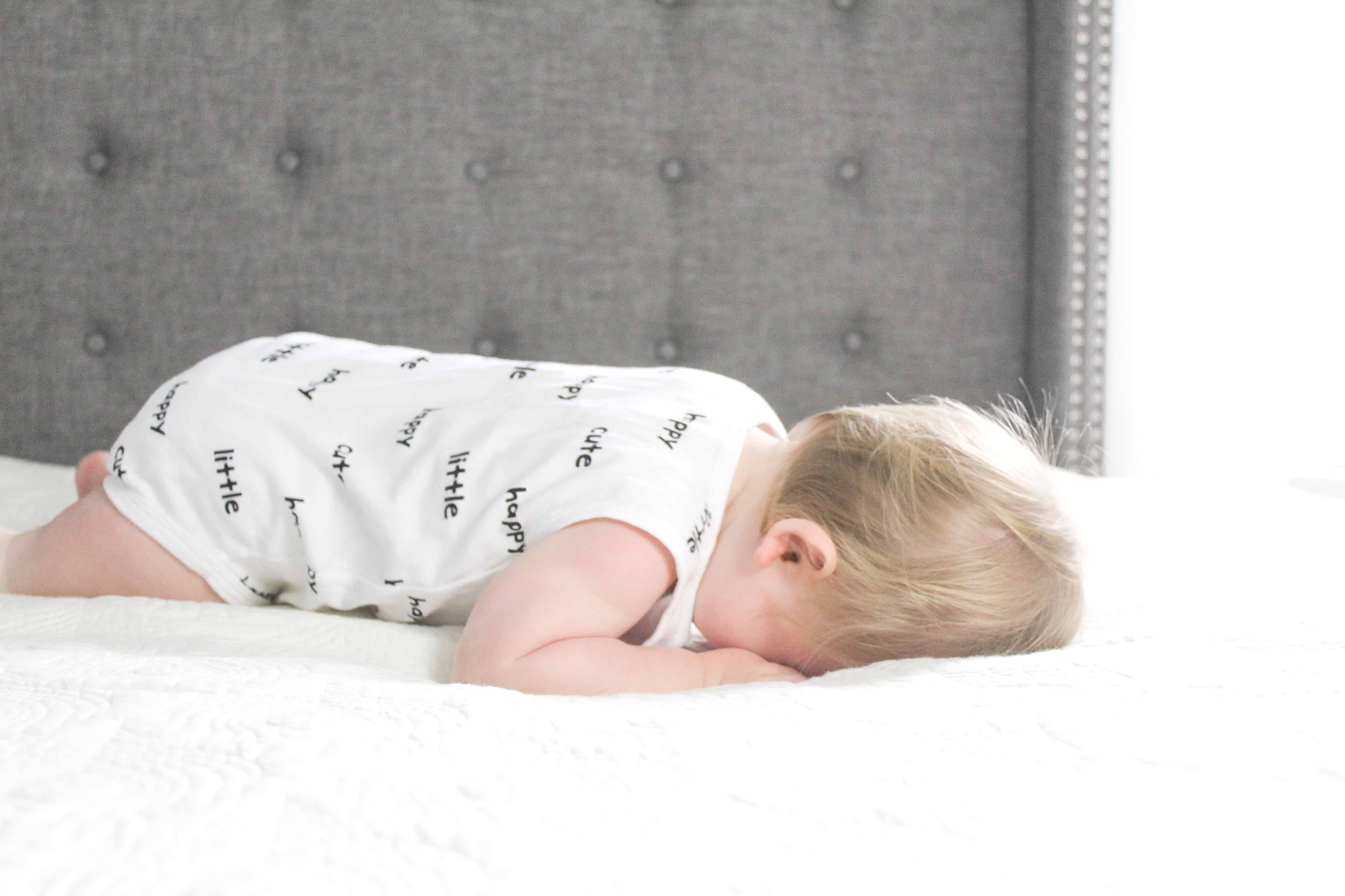 baby laying on bed in carters onsie
