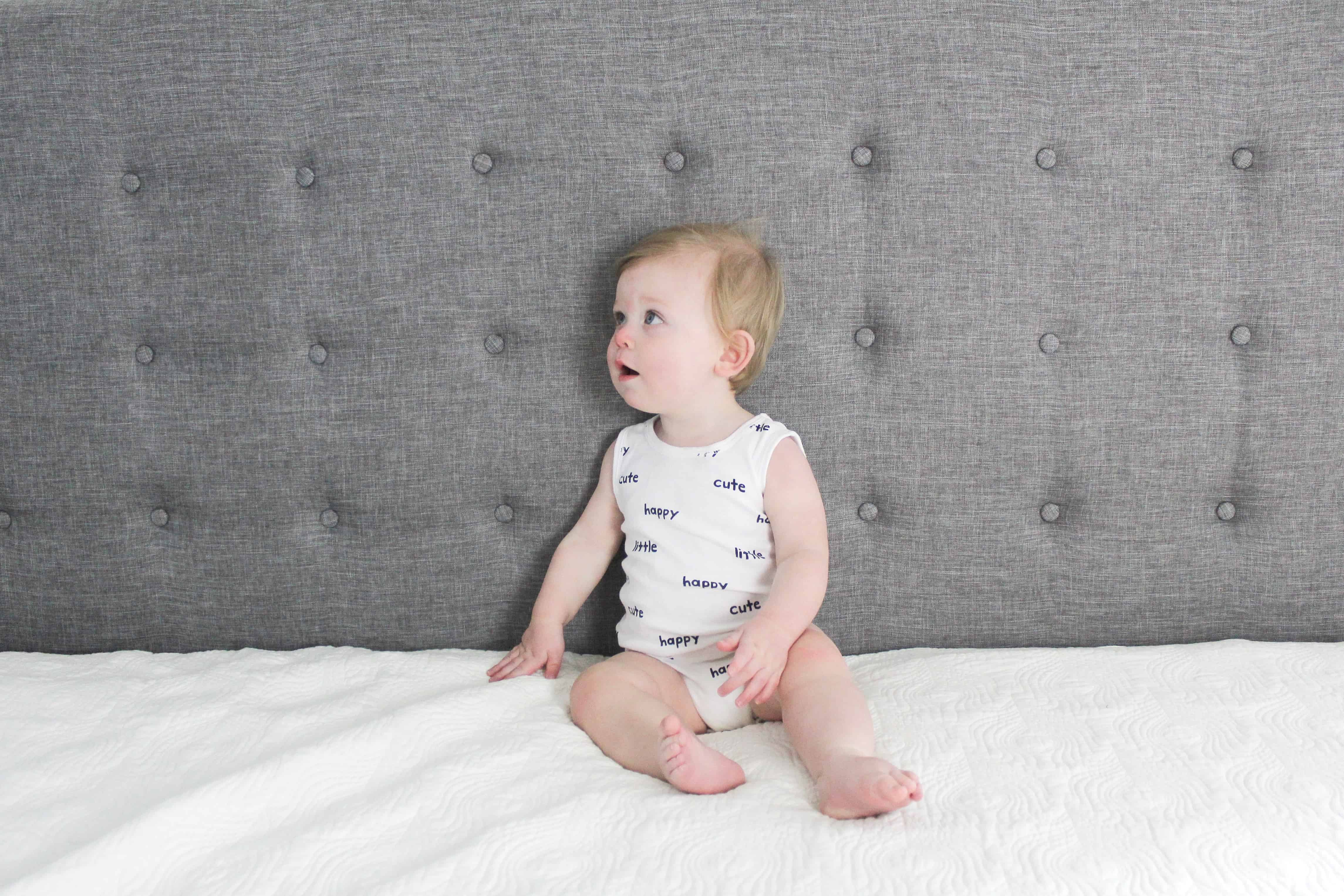 baby in white carters onsie sitting on bed