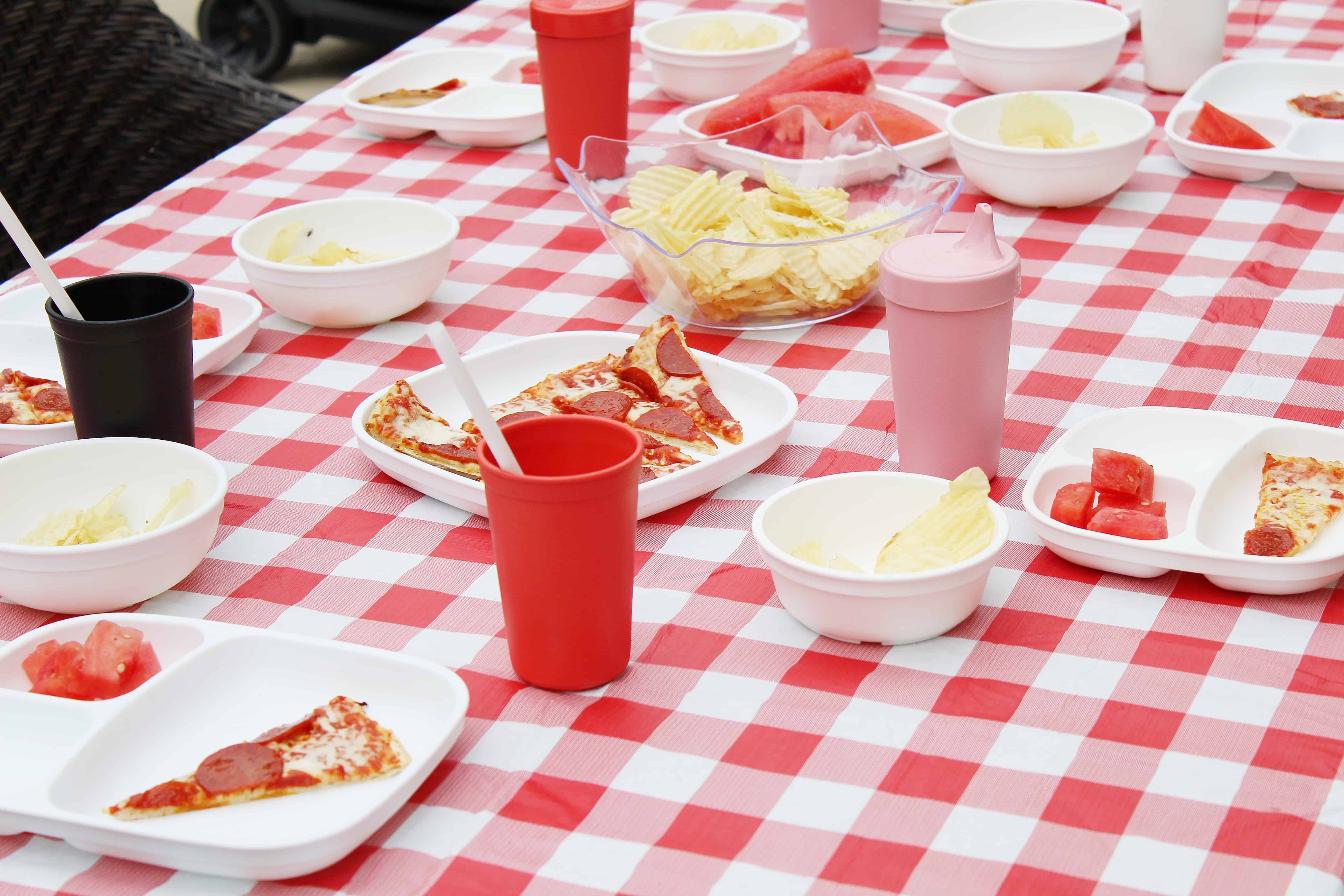 red and white table cloth with plates and cups