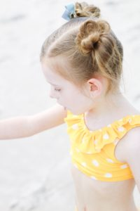 little girl in yellow swimsuit playing on beach