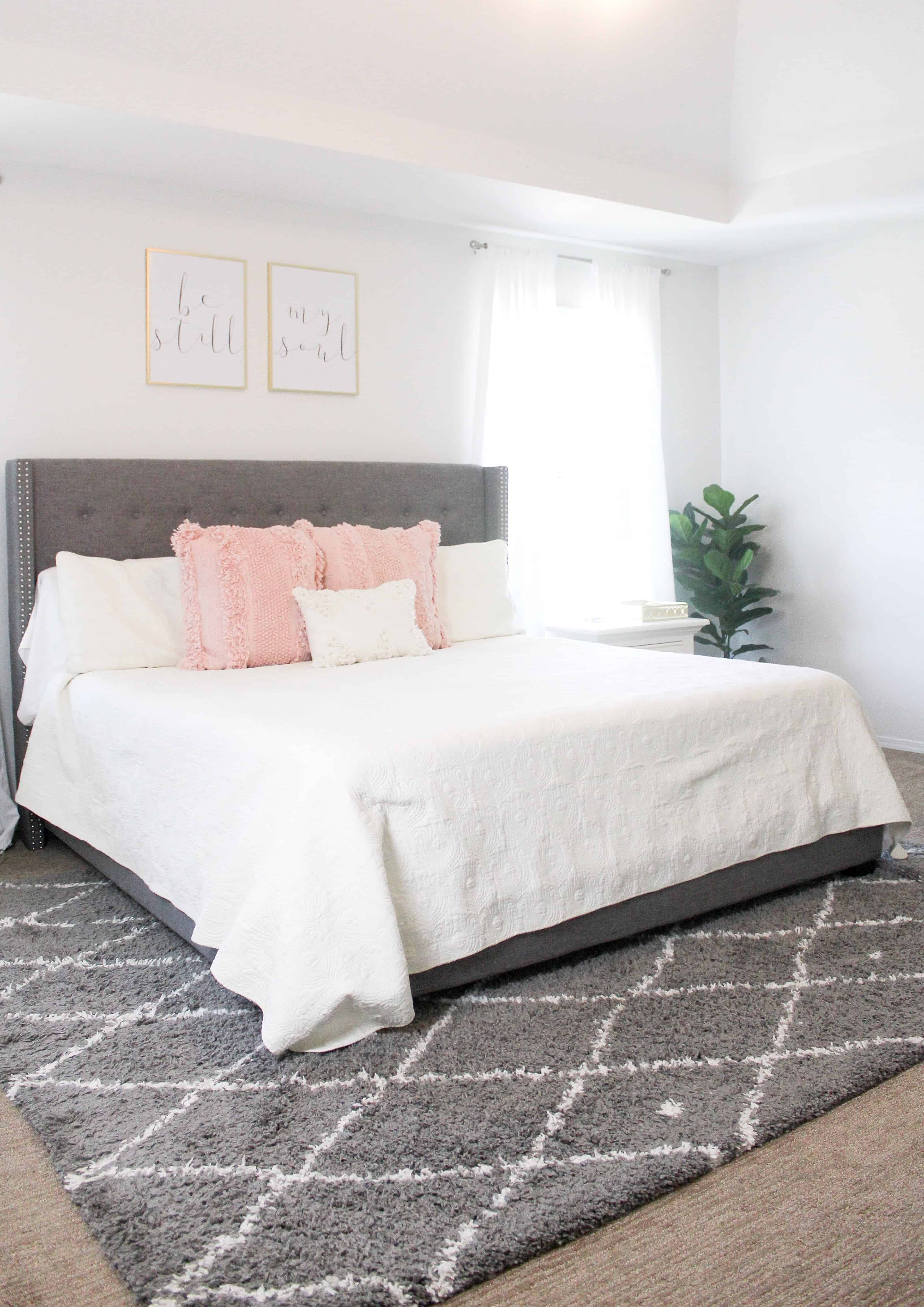 white bedding with pink pillows and grey rug