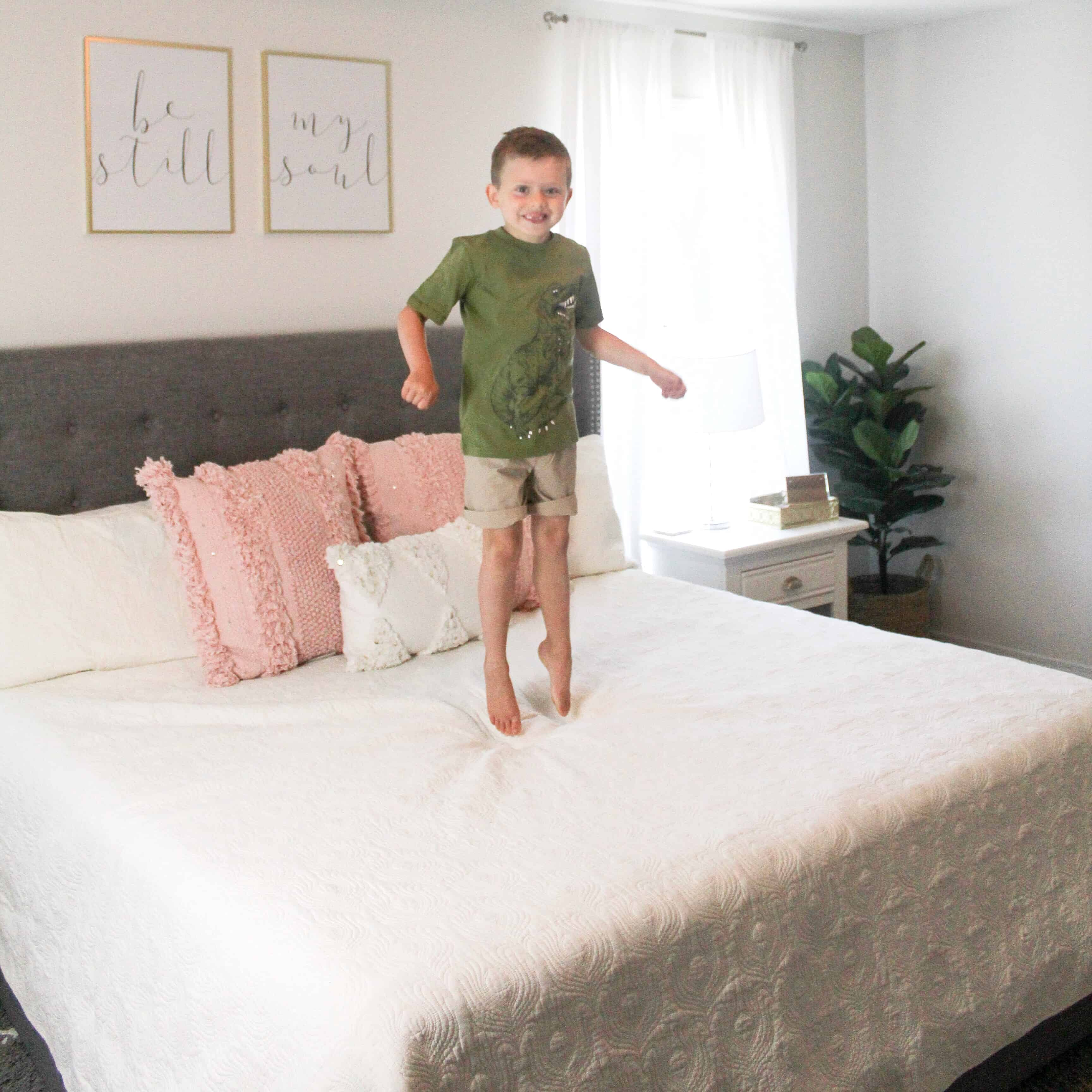 Little boy jumping on bed in Carter's Clothes