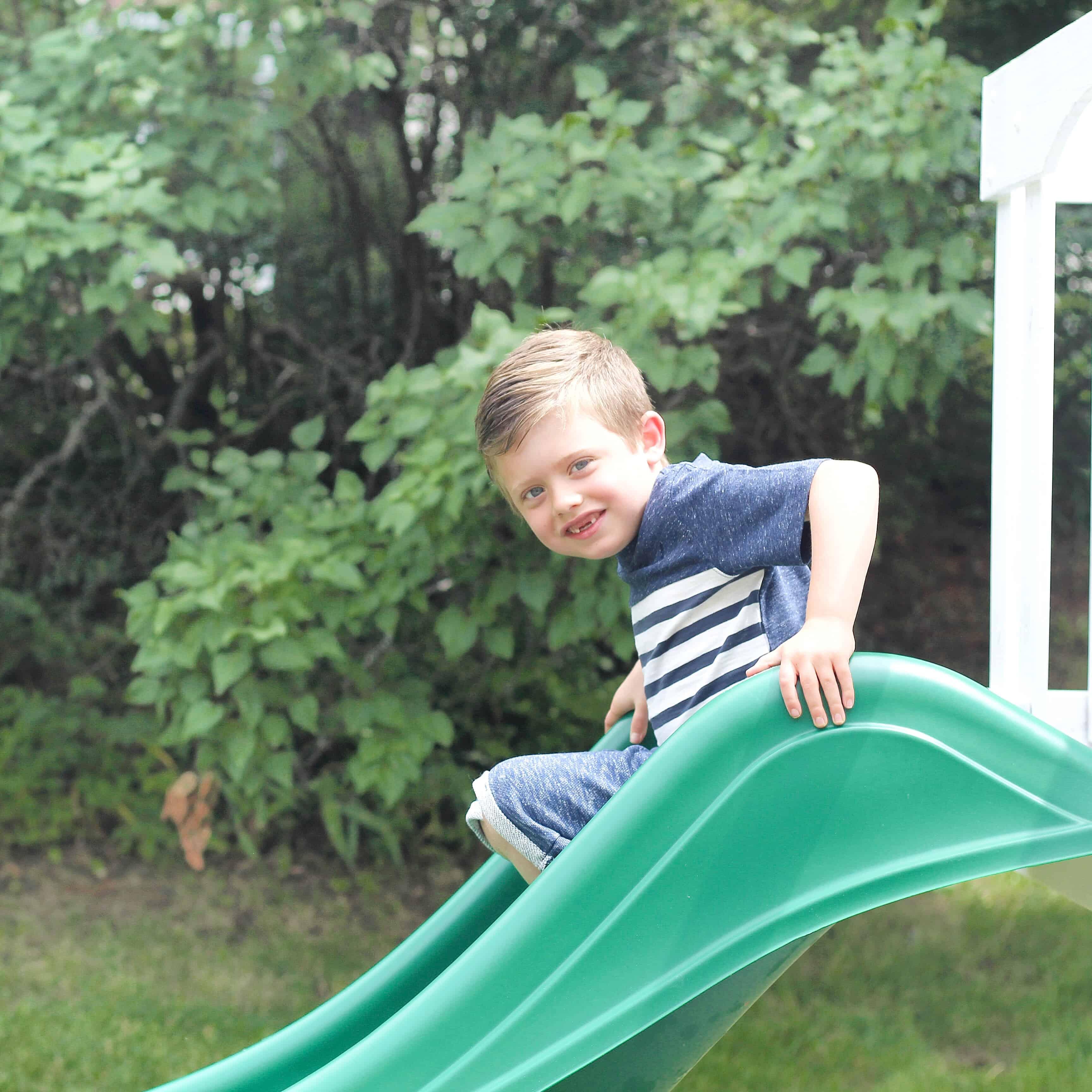 little boy going down the slide