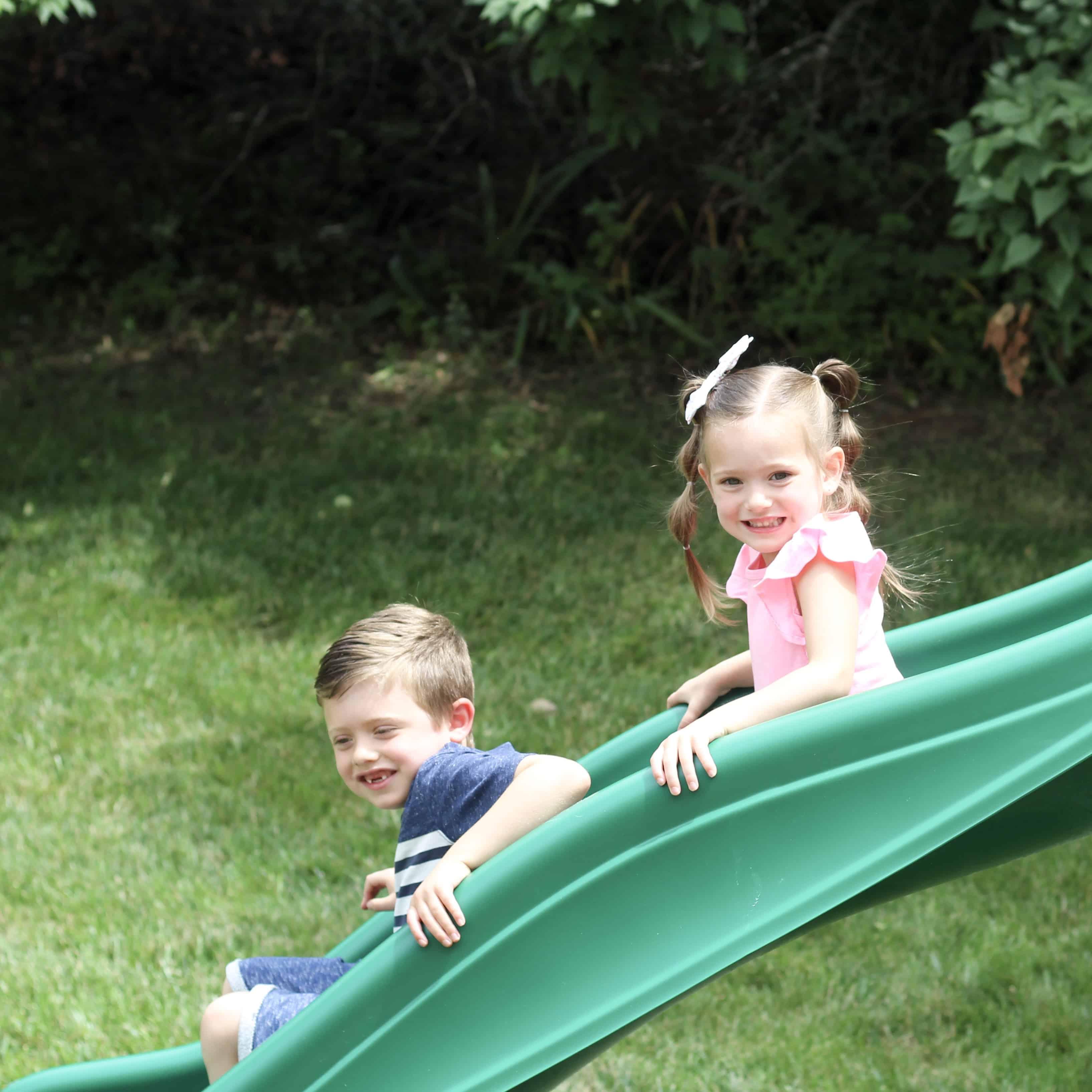 siblings going down slide