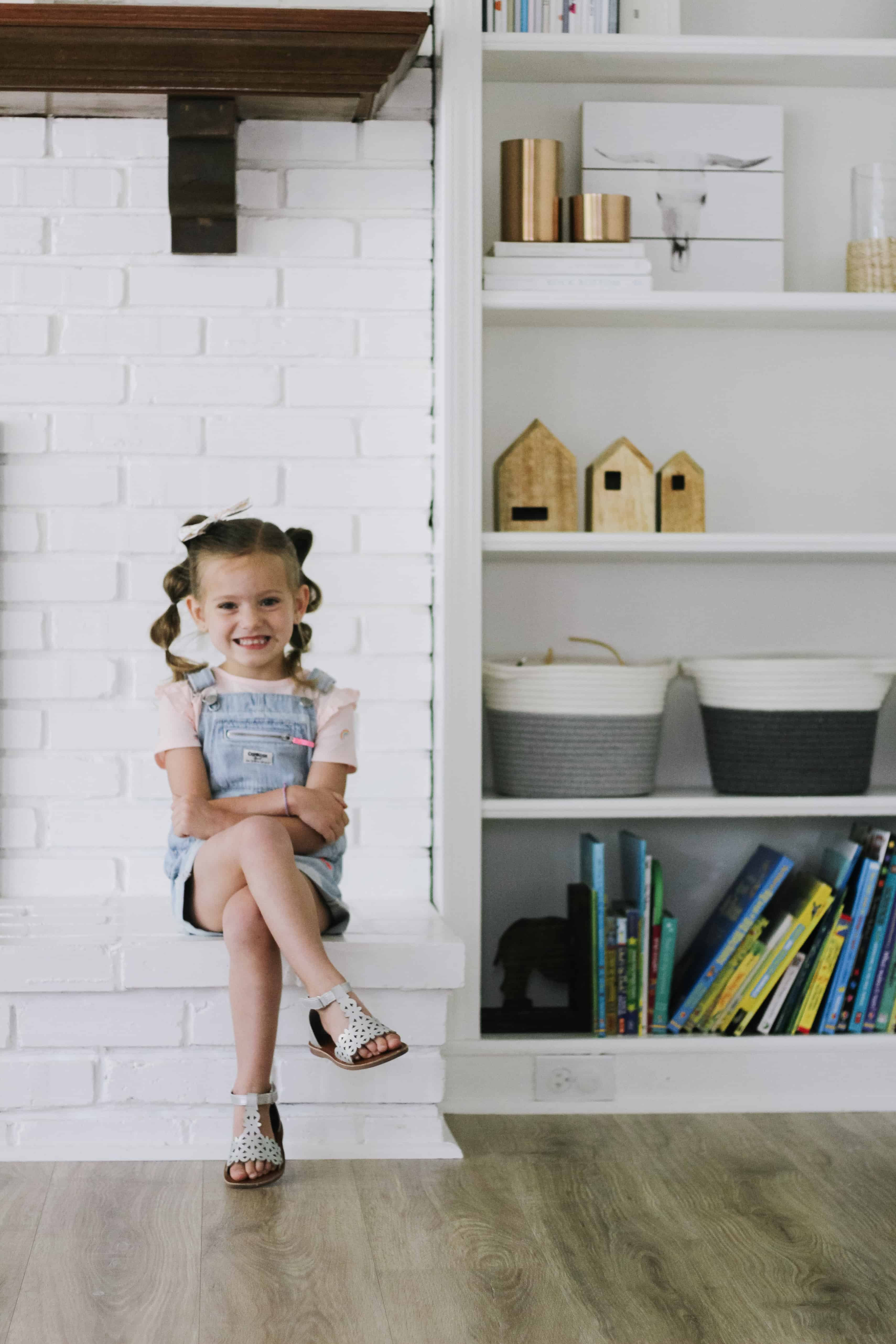 toddler girl sitting on white fireplace