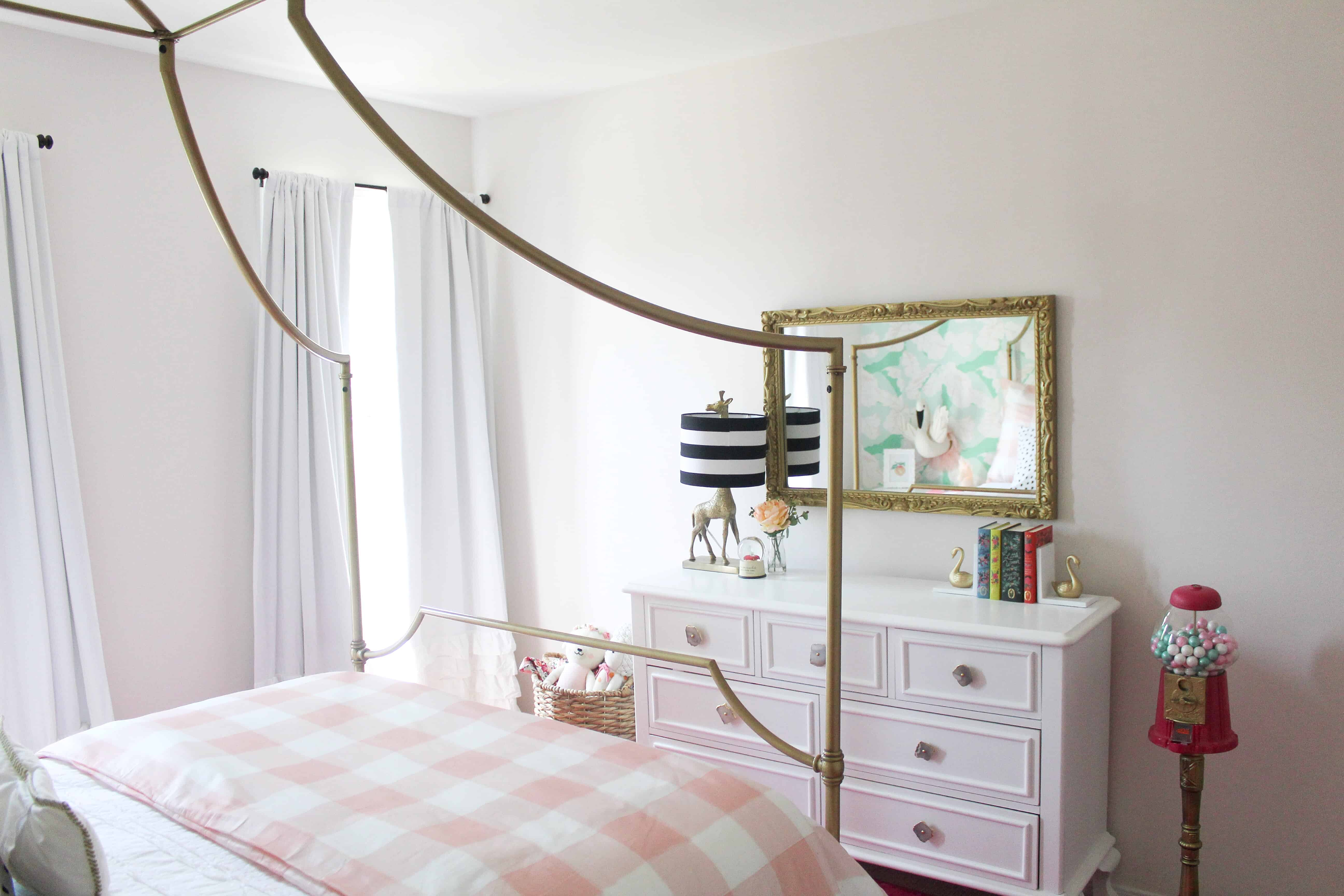 Toddler girl room with gold mirror and bed