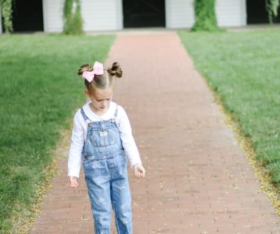 toddler girl in OshKosh overalls