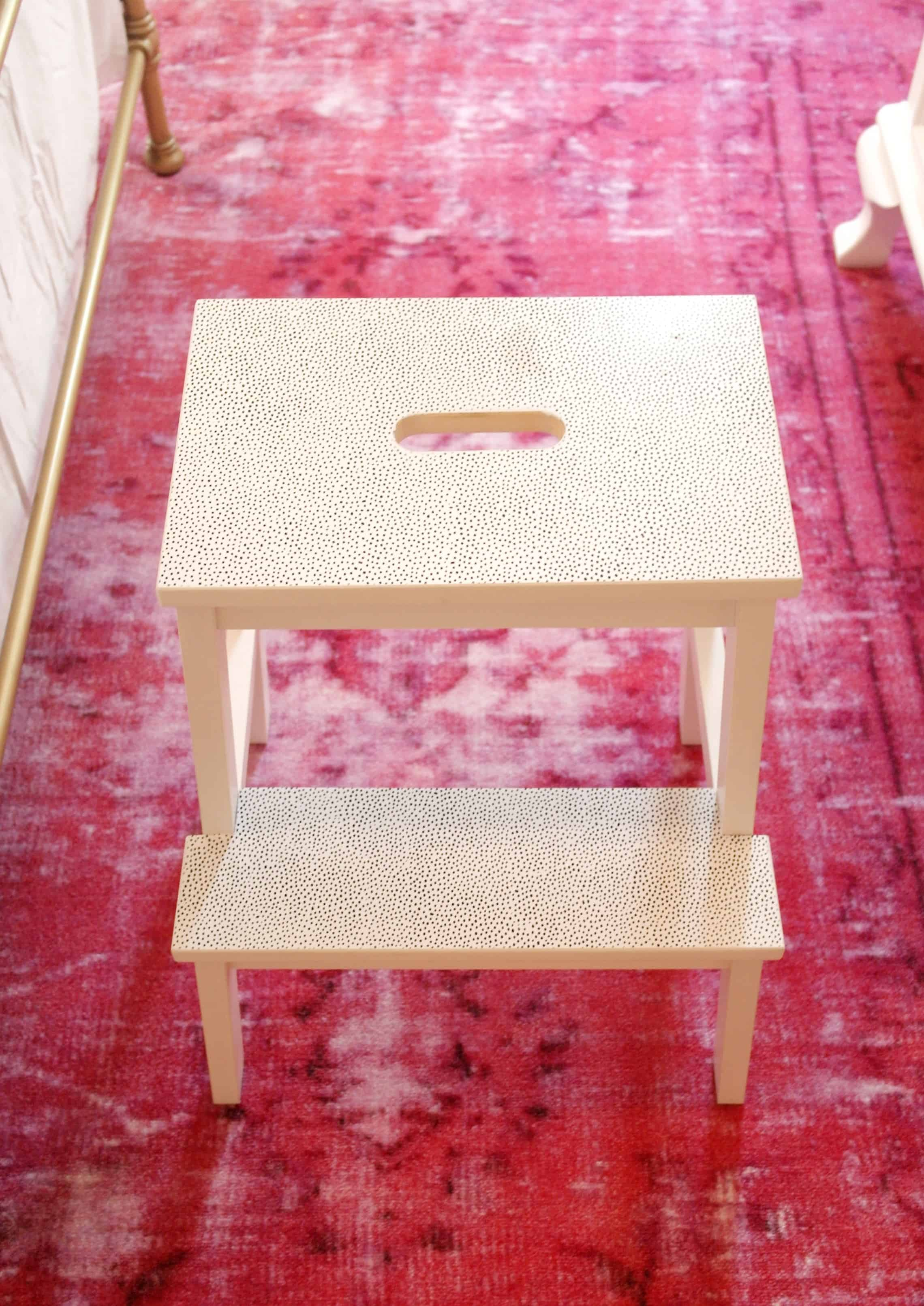 black and white Ikea step stool on pink rug