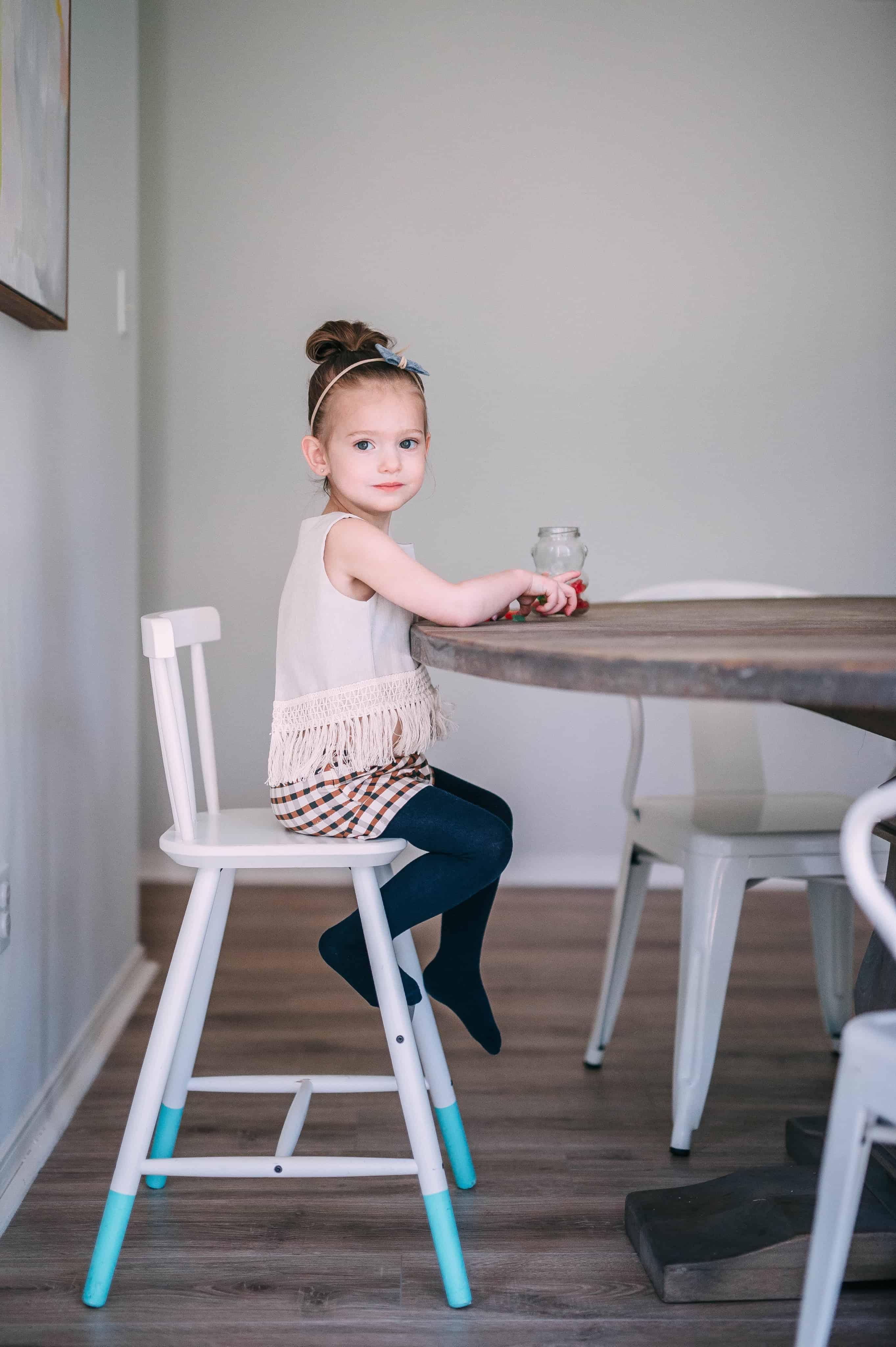 toddler girl sitting at table