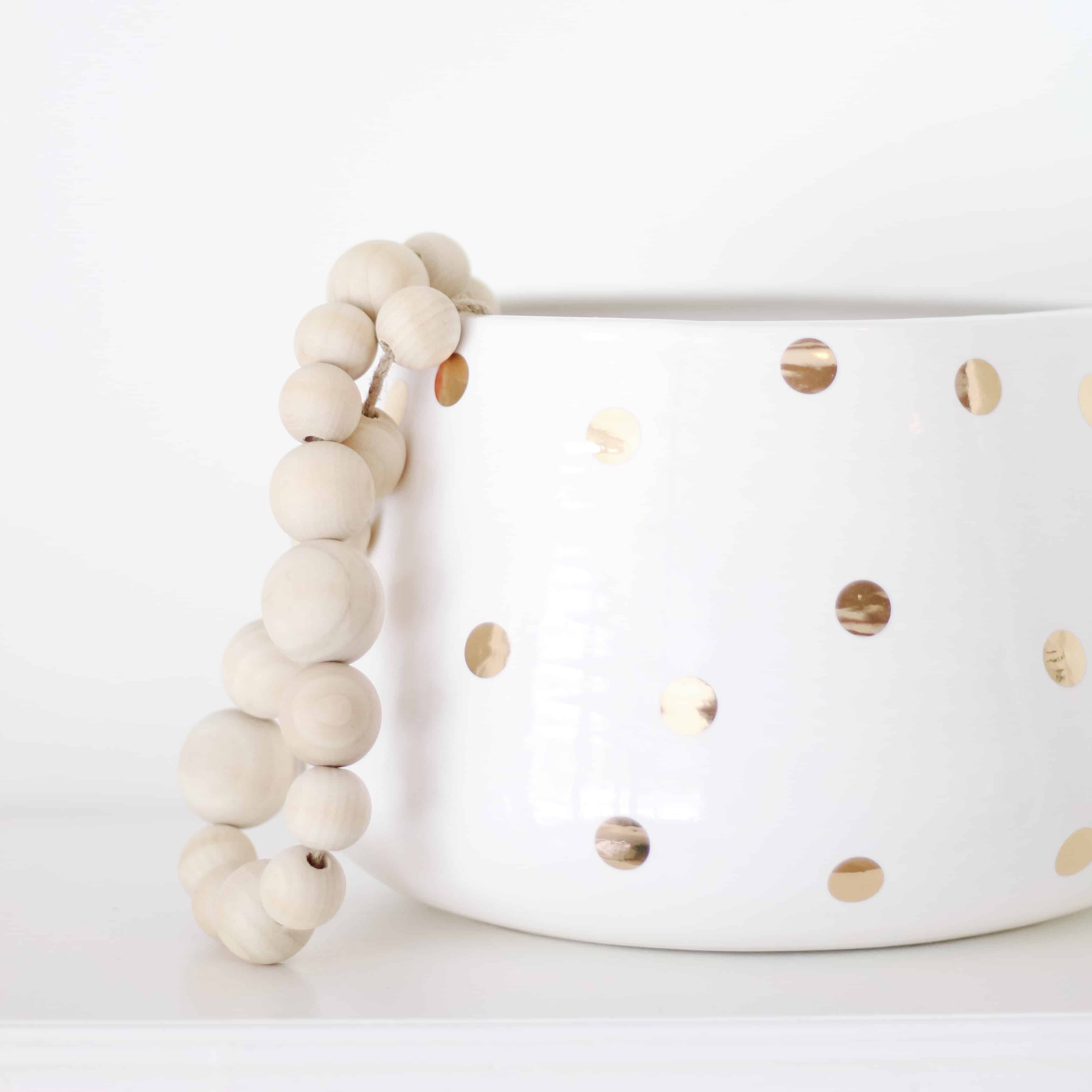 White and gold vase with wood bead strand