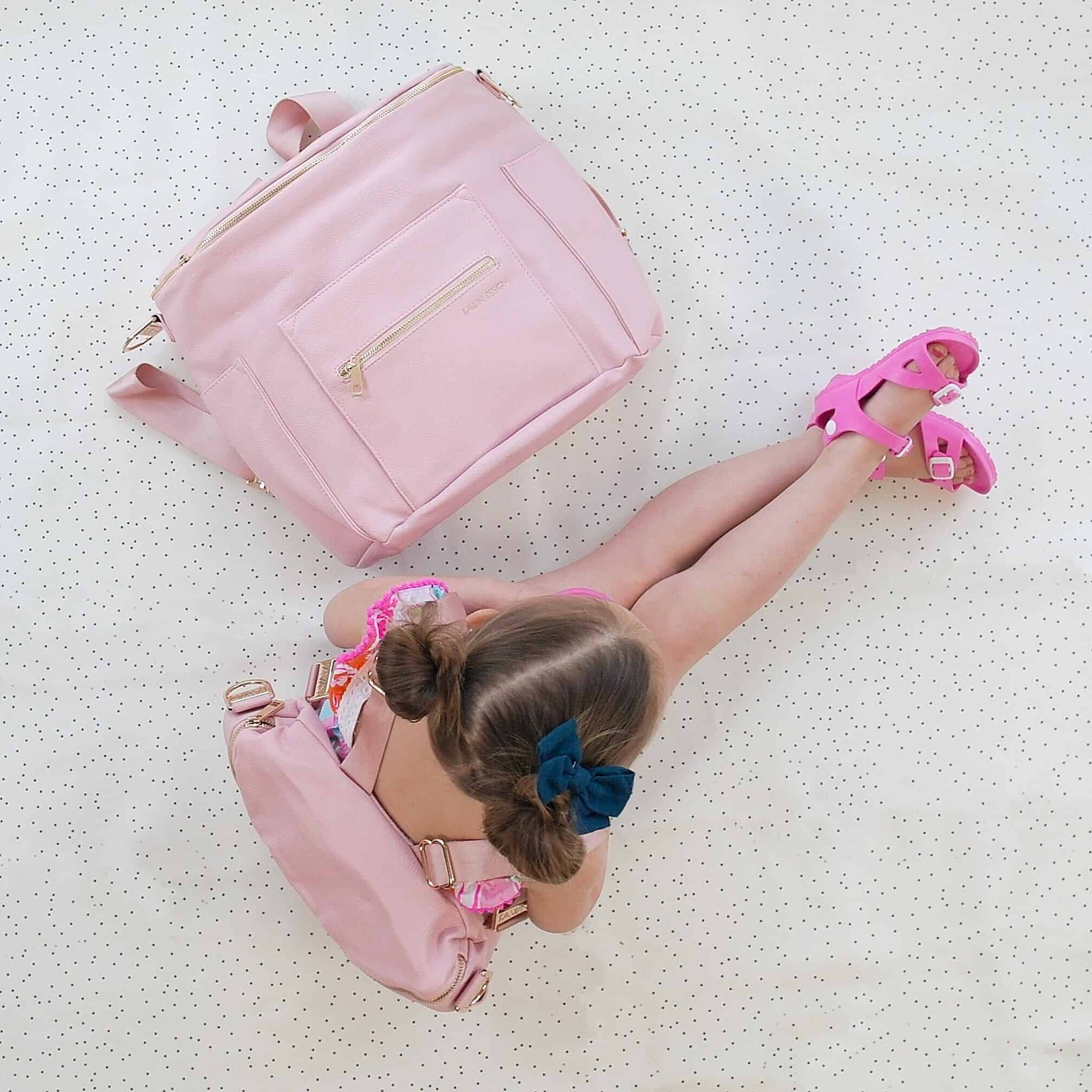 Toddler girl with pink fawn design diaper bag on and pink fawn design diaper bag next to her