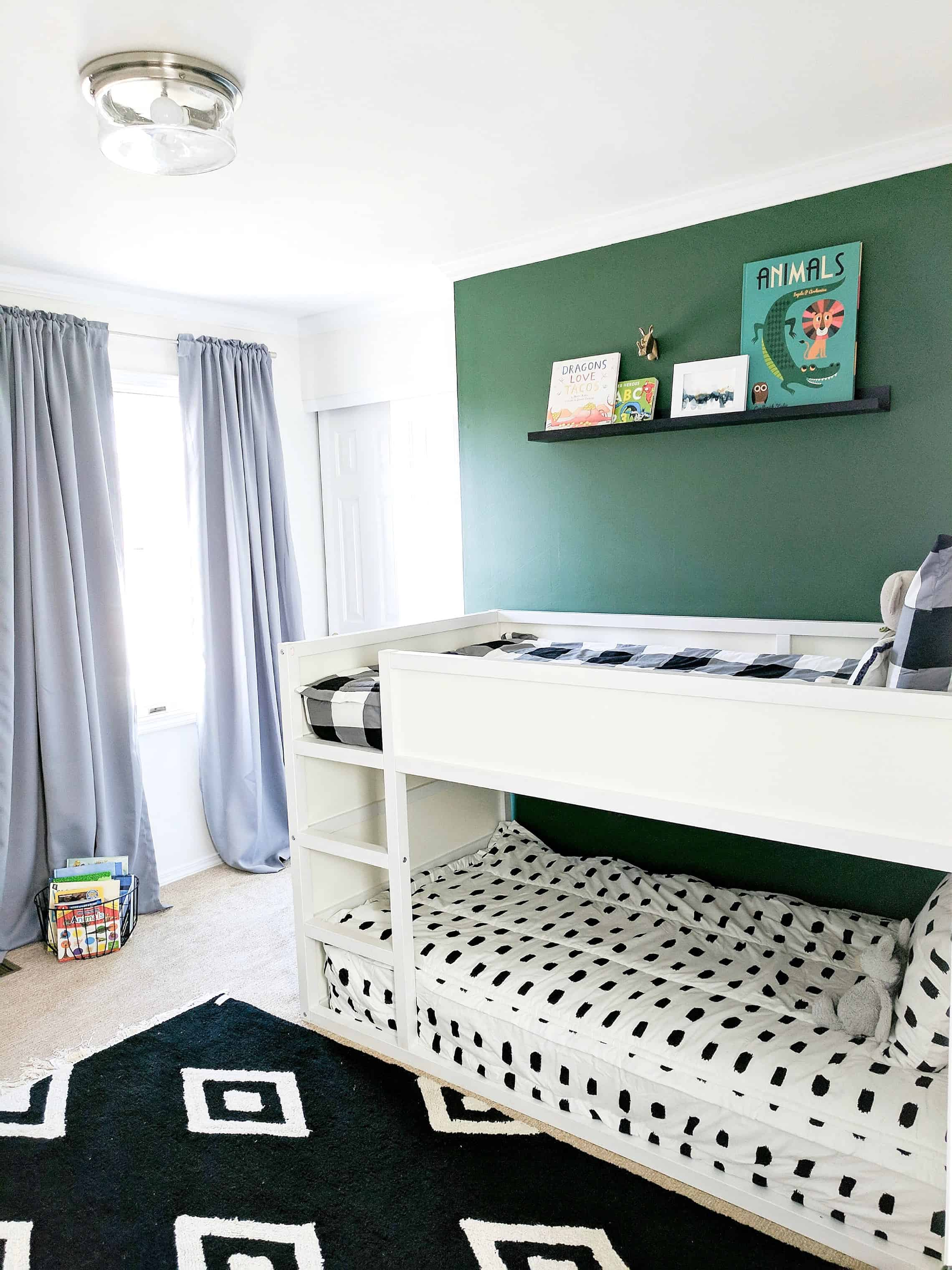 Green wall behind white bunk beds
